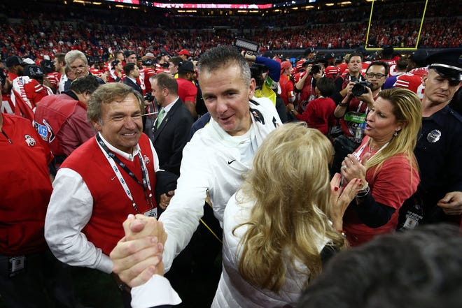 Ohio State football coach Urban Meyer, with wife Shelley to his right, receives congratulations inside Lucas Oil Stadium in Indianapolis after his Buckeyes beat Northwestern 45-24 in the Big Ten Championship Game on Dec. 1.