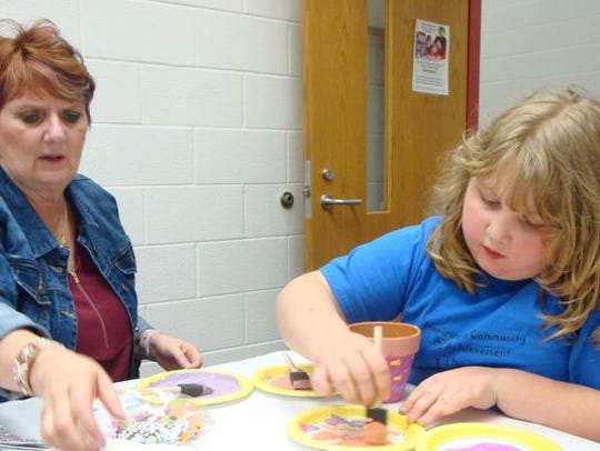 YMCA mentor Maryjo Mundey, left, and Kendra Paluscsak work on a craft project as part of Marion Mentors 21.