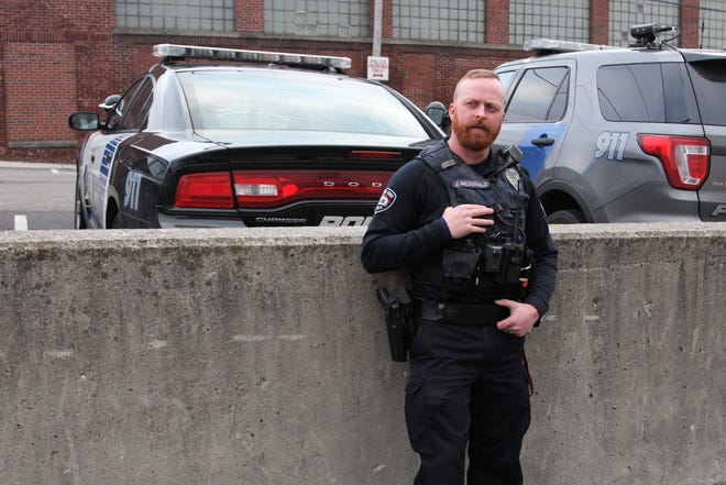 Marion Police Officer Joseph McDonald stands next to a police cruiser, on the right, that had been struck during an 11 second firefight on Patterson Street over the summer. McDonald had gone to the address for a wellness check after a 30-year-old woman had been shot twice earlier that day.