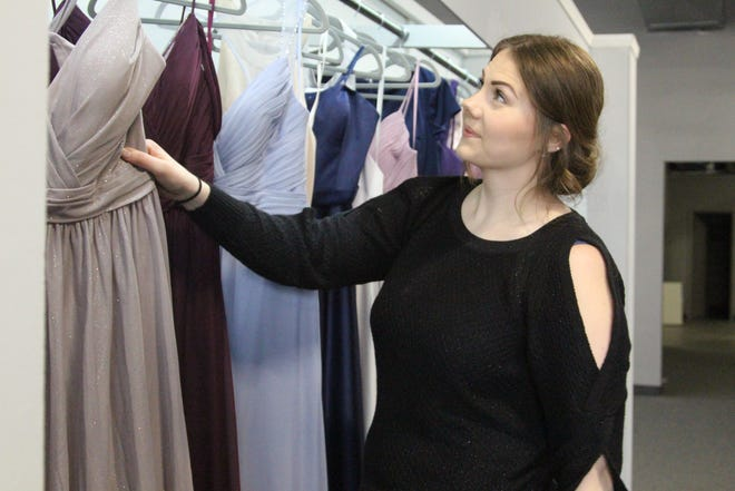 Shana Riedlinger arranges bridesmaid dresses Friday at Avenue 42, a new bridal and formal wear shop downtown at the corner of Center and Orchard streets. The shop opened its doors for the first time on Wednesday.