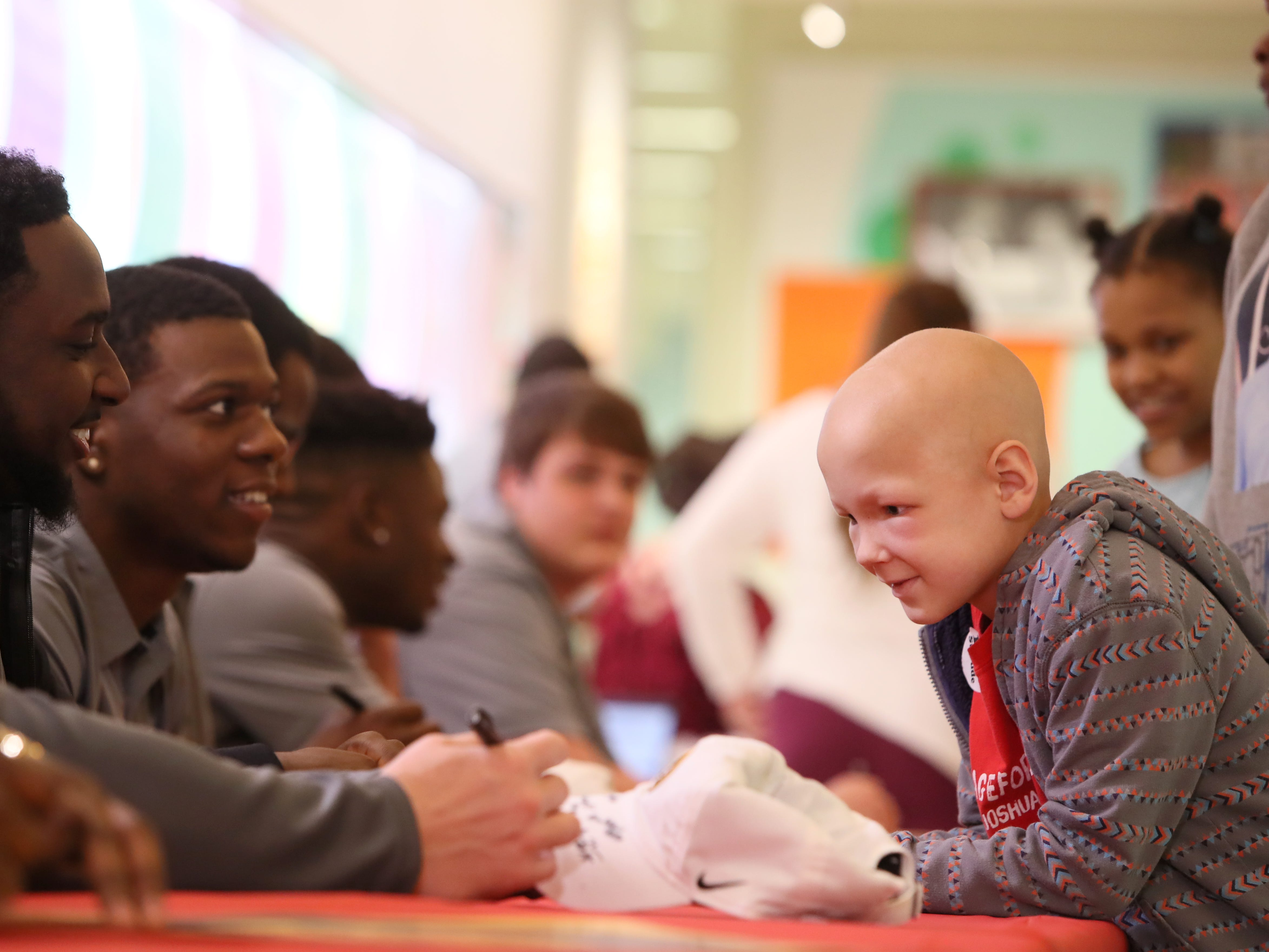St. Jude patient Cohen has a poster signed by the Missouri Tigers football team Friday as the players made a visit to the hospital as a part of their tour of Memphis, before playing in Monday's Liberty Bowl.
