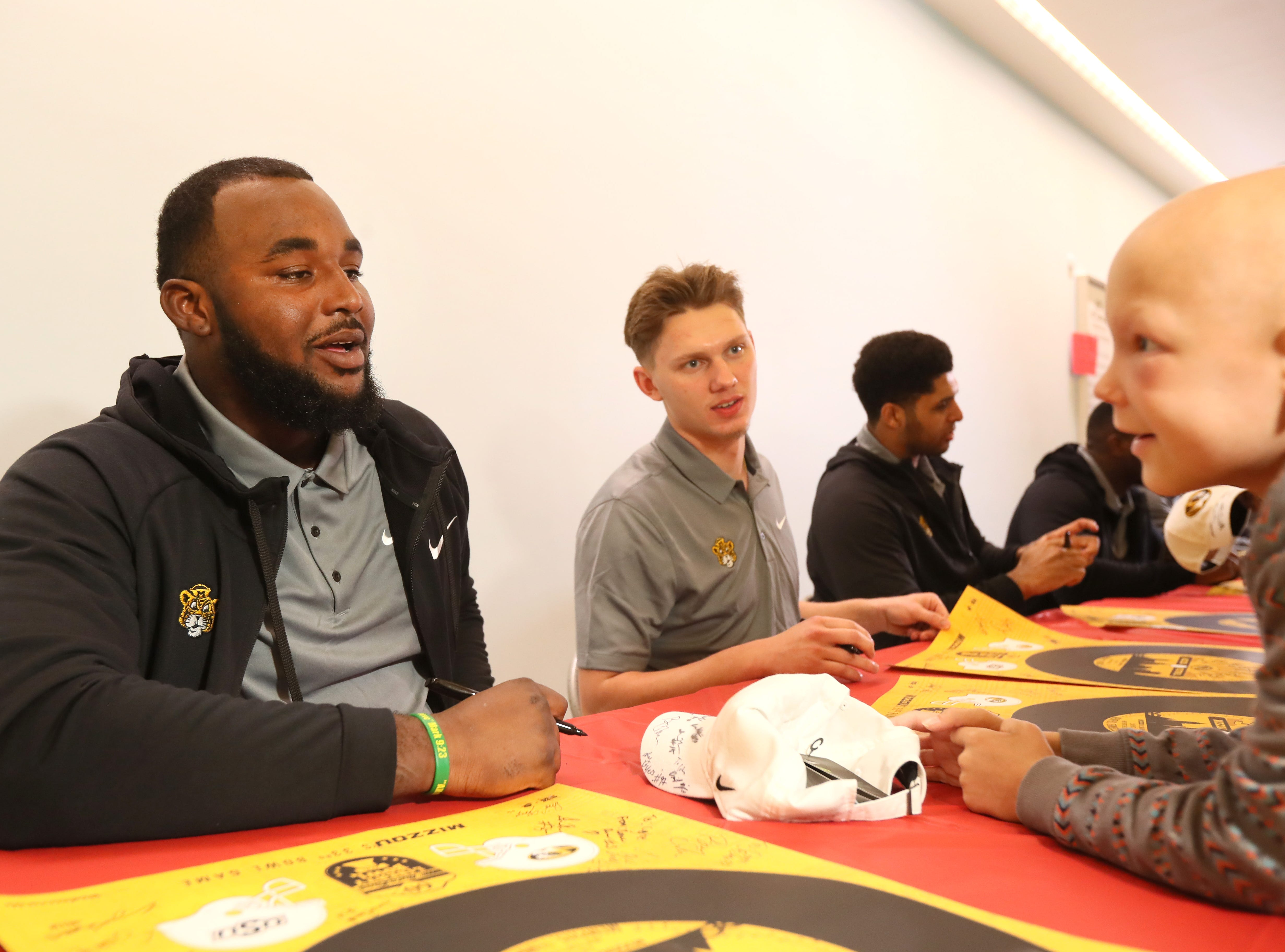 Missouri Tigers football defensive End Akial Byers signs a poster for St. Jude patient Cohen on Friday as the players made a visit to the hospital as a part of their tour of Memphis, before playing in Monday's Liberty Bowl.