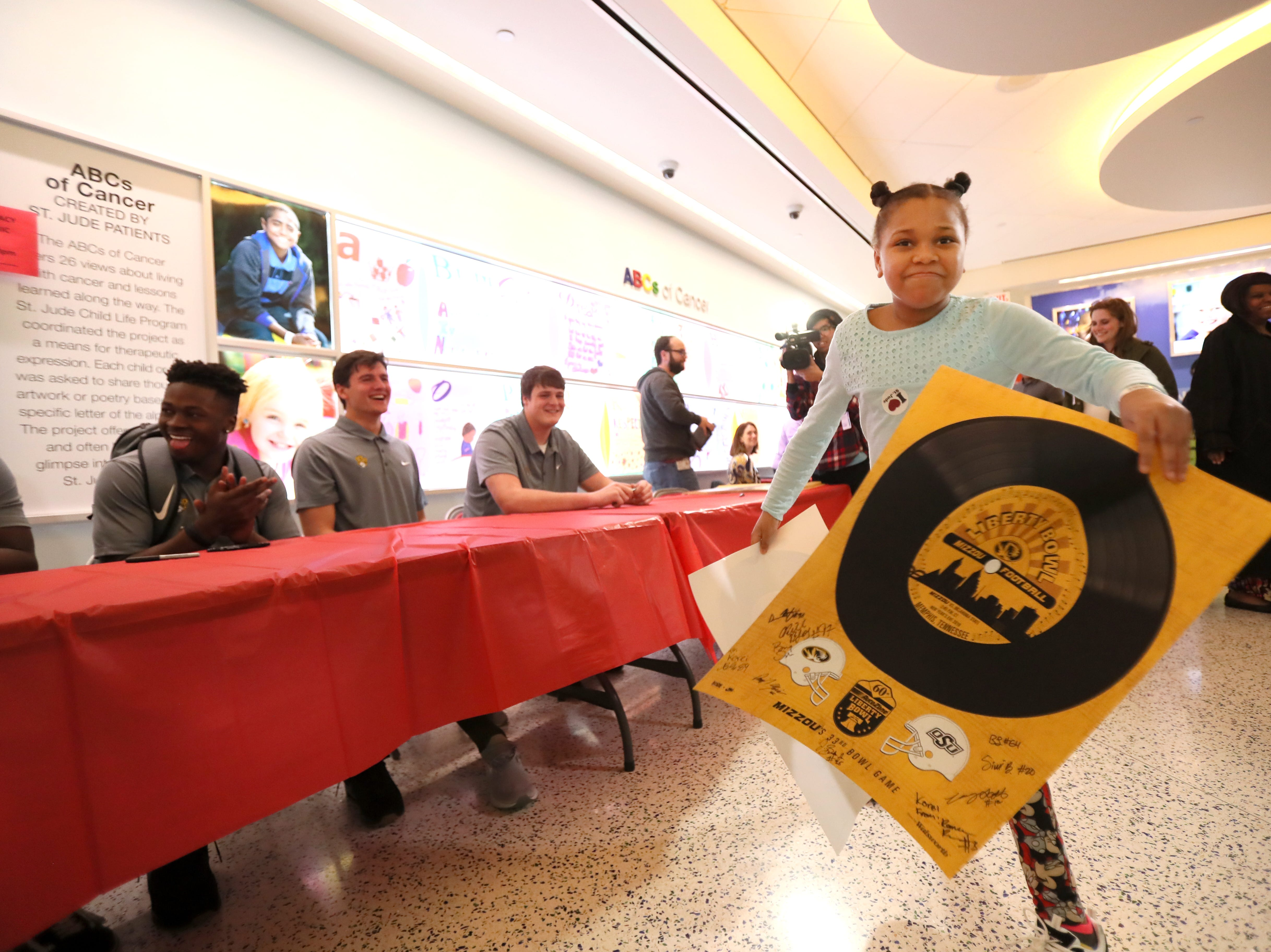 St. Jude patient Korei has a poster signed by the Missouri Tigers football team Friday as the players made a visit to the hospital as a part of their tour of Memphis, before playing in Monday's Liberty Bowl.