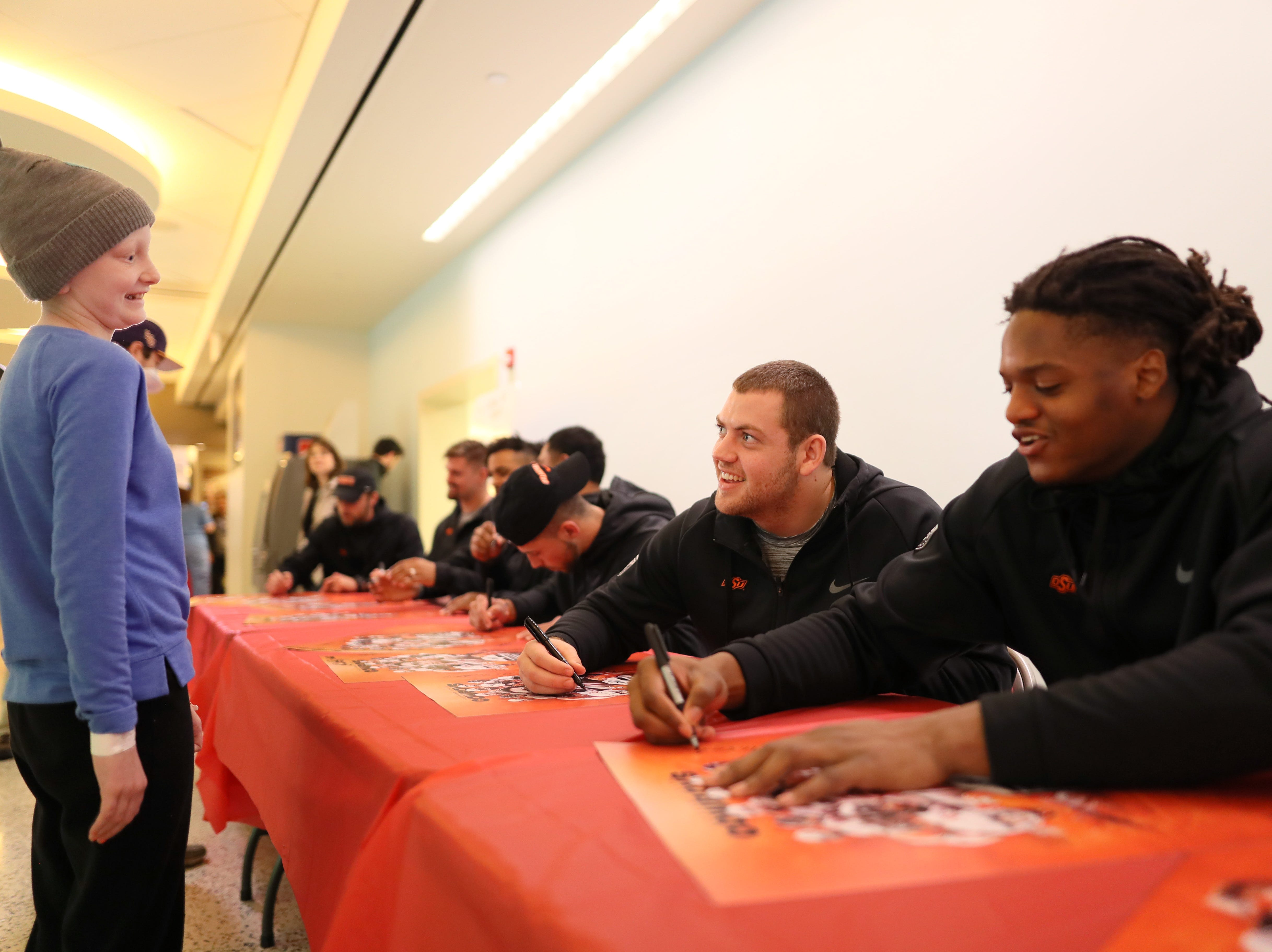 The Oklahoma State Cowboys football team autographs posters for St. Jude patients Friday as the players made a visit to the hospital in part of their tour of Memphis, before playing in Monday's Liberty Bowl.