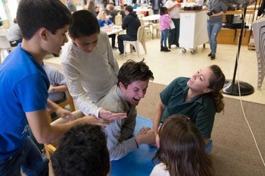 Camp Reunite staff counselor Daniel Brever (center) arm wrestles children of inmates at the Taycheedah Correctional Institution in Fond du Lac, Wis. They were participants in Camp Reunite, a  program that allows children and their incarcerated mothers to spend time together.