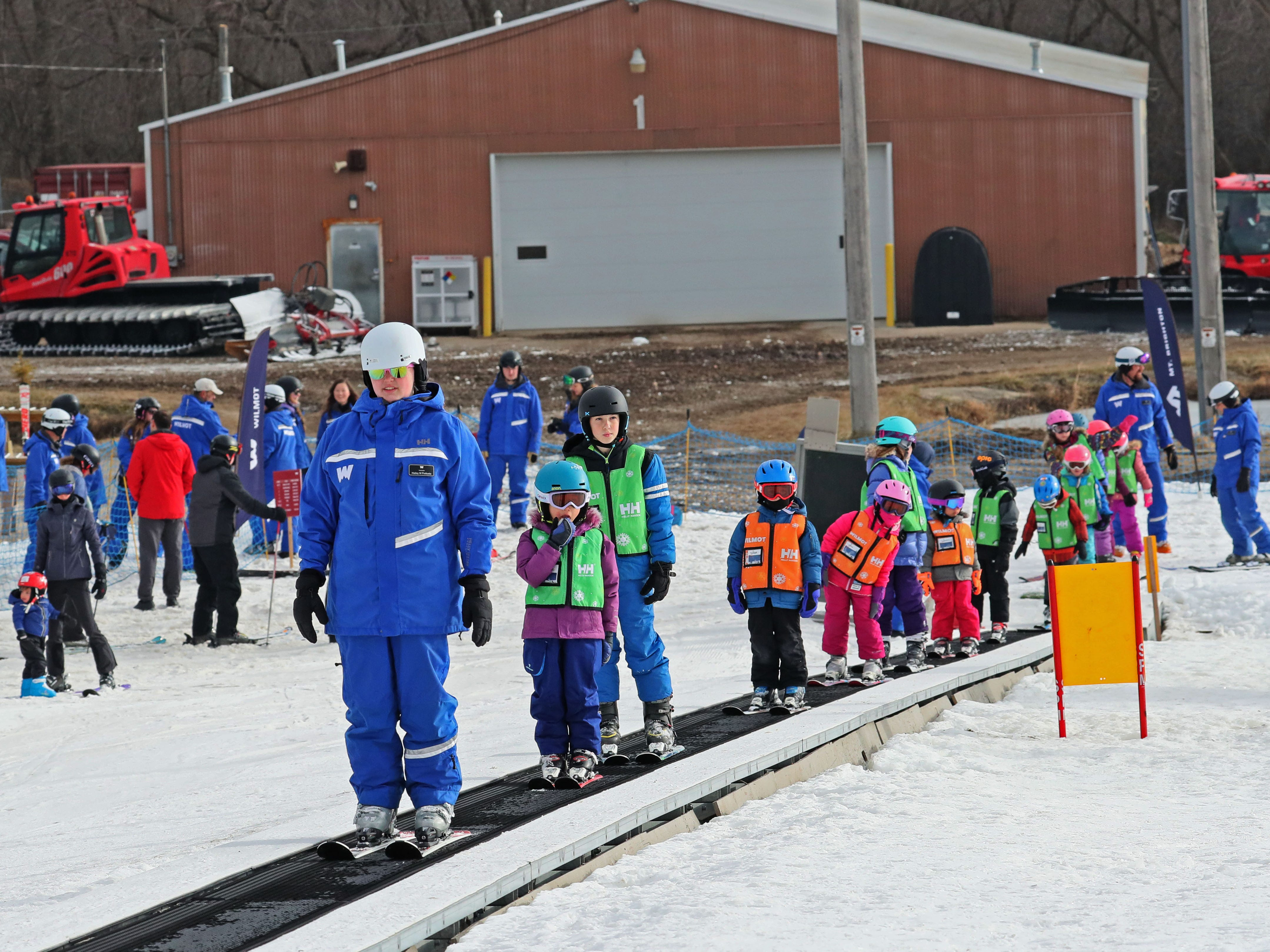 Children at Wilmot Mountain's ski school ride the magic carpet to get up the small hill.