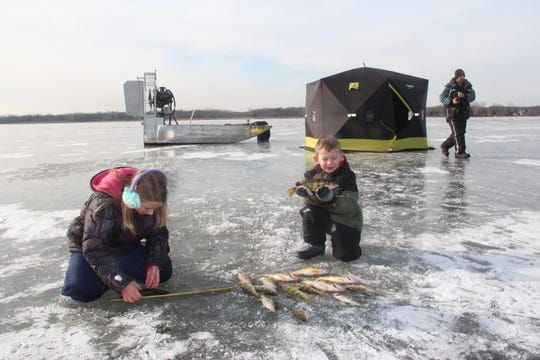 Zach Burgess (right), owner of Why Knot Fishing Charters, moves to check a tip-up while his daughter, Addisyn, and son, Finn, check the growing pile of yellow perch caught on an ice fishing outing on Green Bay. The group accessed the location with an airboat (back left) made by Burgess.