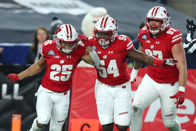 Wisconsin's Eric Burrell (25) and Chris Orr (54) celebrate Burrell's interception in the first quarter of the Pinstripe Bowl on Thursday. Orr also had an interception in the game.