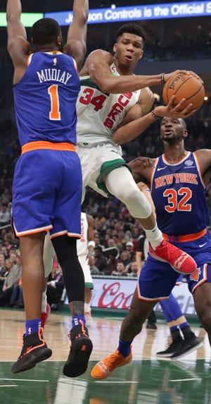 Giannis Antetokounmpo  makes a pass around  Knicks guard Emmanuel Mudiay on Thursday night.