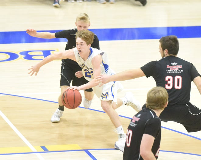 Mountain Home's Wyatt Gilbert drives between Mountain Home Christian Academy's Caleb Bingham and Matt Woods during the Bombers' victory Thursday night at The Hangar.