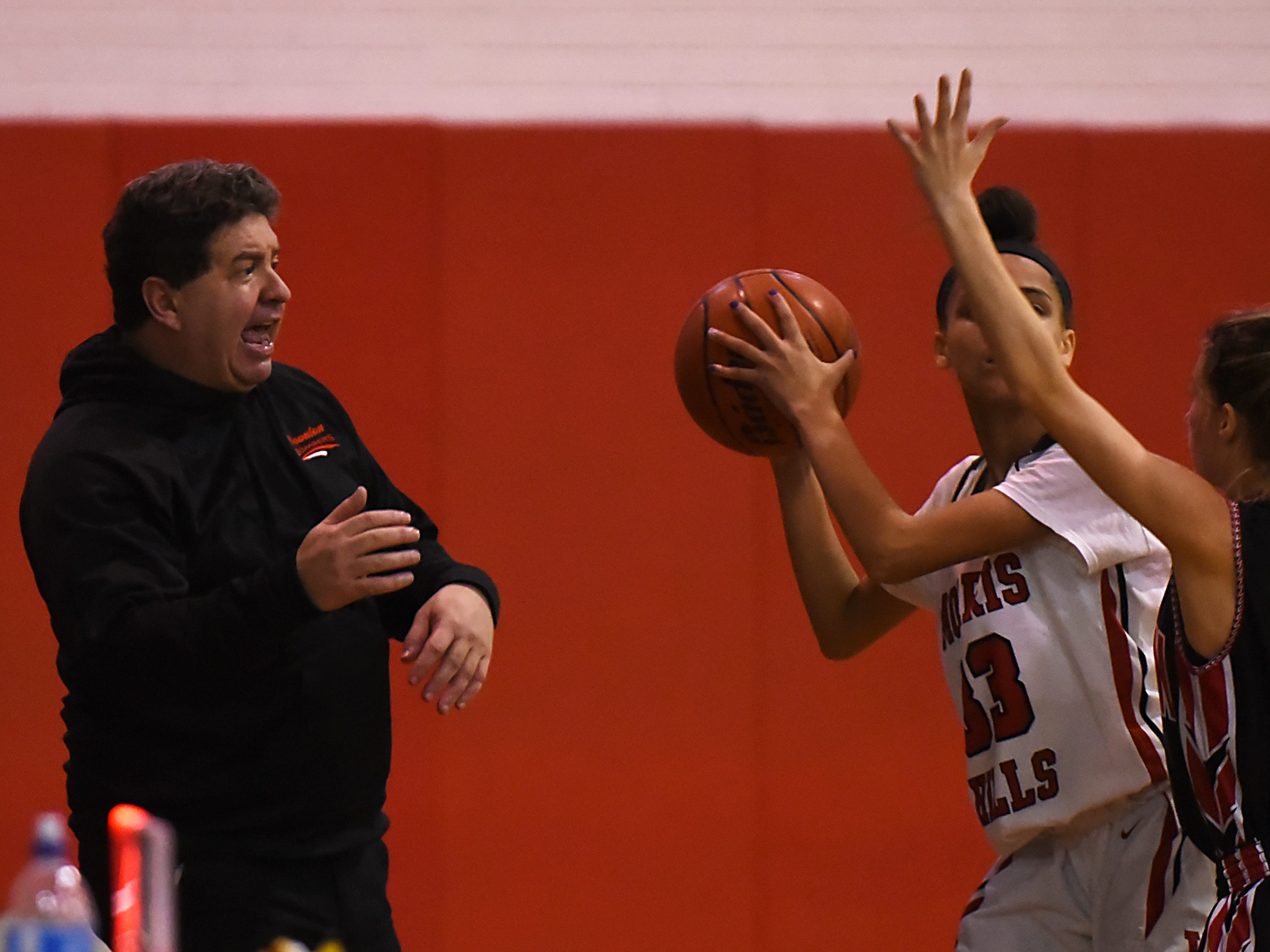 Boonton coach Mike Carlin gives instructions as Morris Hills' Mackenzie Creistonand tries to pass the ball past Boonton senior Nicole Krozser.  Boonton Vs. Morris Hills girls basketball game at the Morris Hills Holiday Tournament in Rockaway on Friday December 28, 2018. (From left)