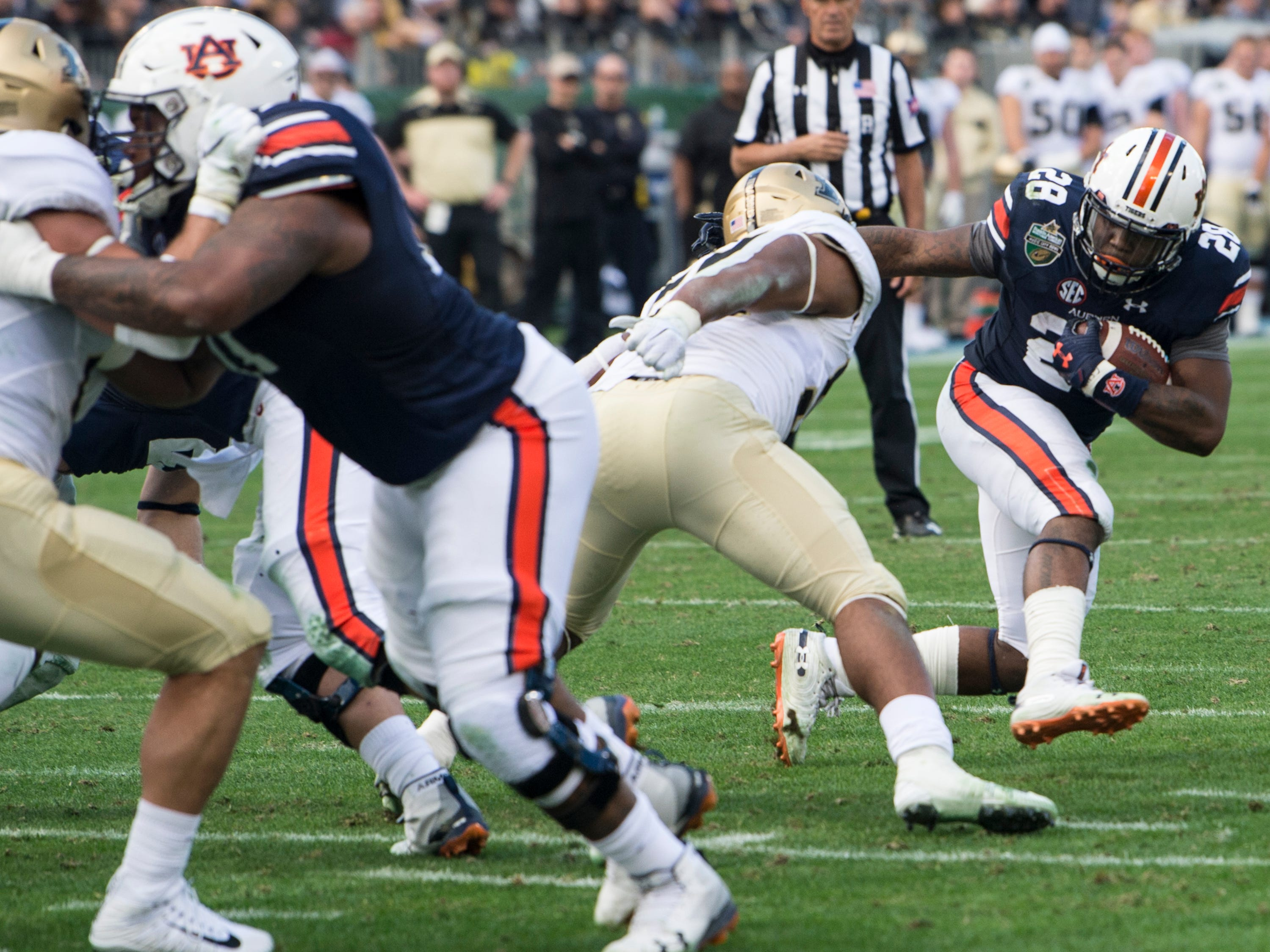 Auburn running back JaTarvious Whitlow (28) is stopped in the backfield by Purdue linebacker Derrick Barnes (55) during the Music City Bowl at Nissan Stadium in Nashville, Tenn., on Friday, Dec. 28, 2018. Auburn defeated Purdue 63-14.