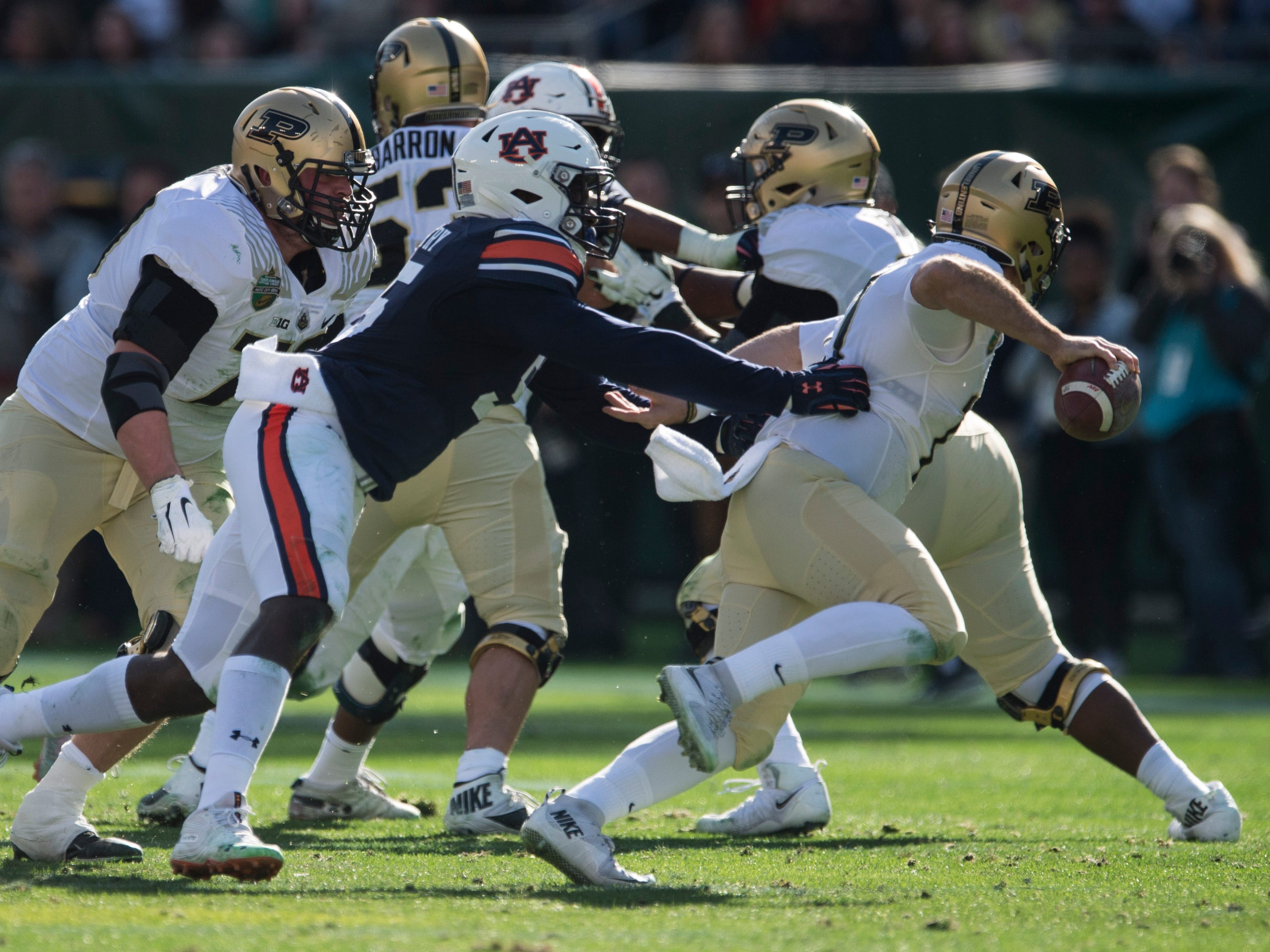 Auburn defesnive lineman T.D. Moultry (55) chases Purdue quarterback David Blough (11) in the backfield during the Music City Bowl at Nissan Stadium in Nashville, Tenn., on Friday, Dec. 28, 2018. Auburn defeated Purdue 63-14.