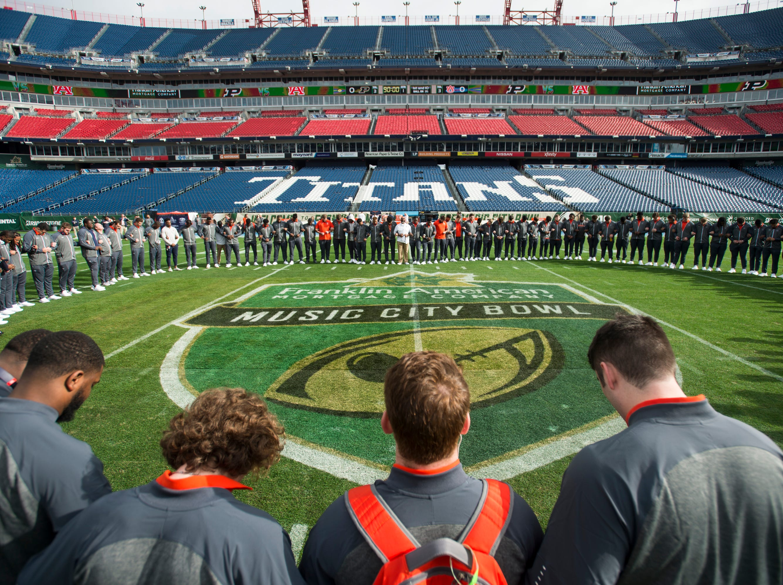 Auburn players pray on the field before taking on Purdue in the Music City Bowl at Nissan Stadium in Nashville, Tenn., on Friday, Dec. 28, 2018.