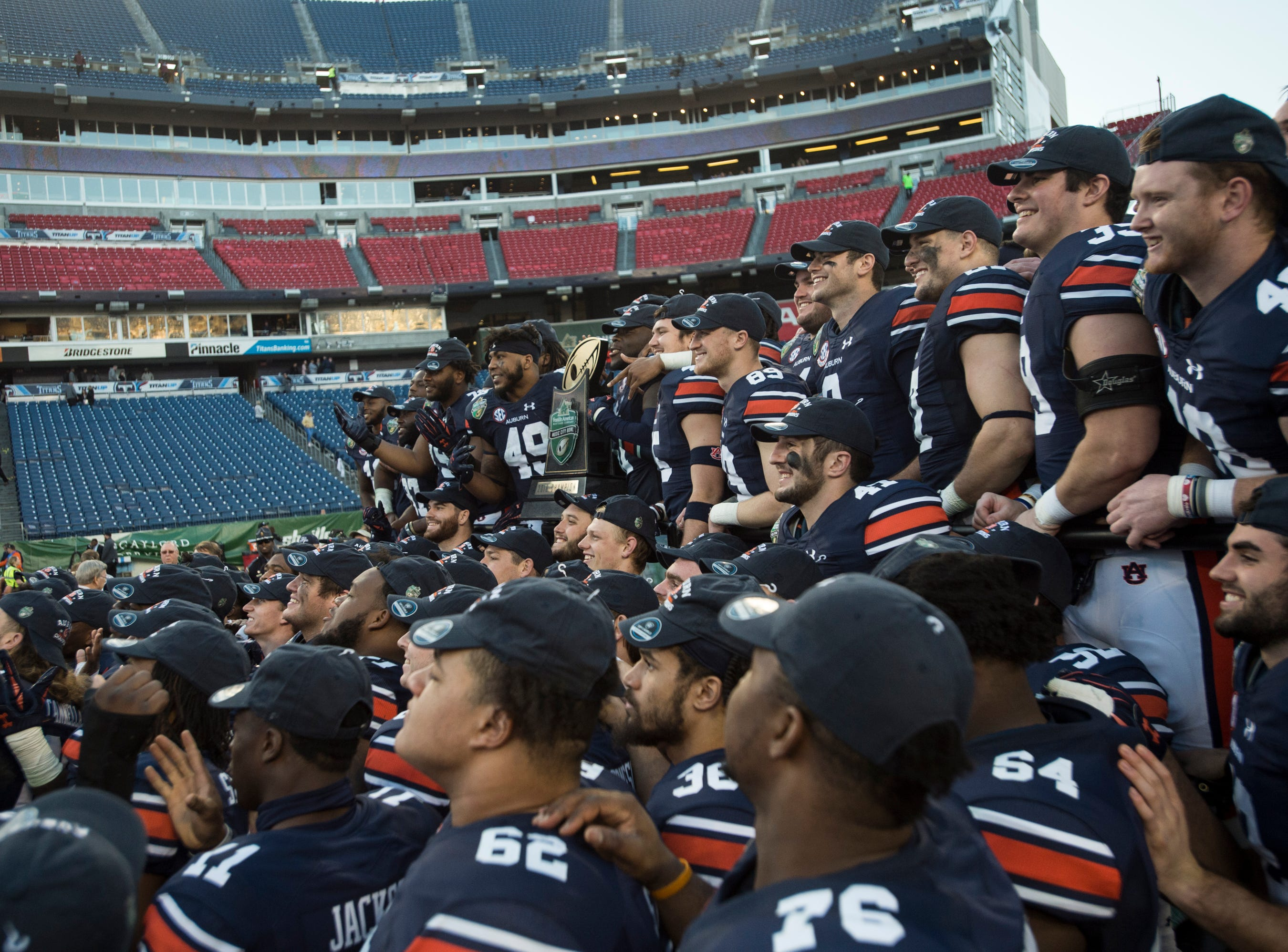 Auburn players pose for a picture at the end of the game during the Music City Bowl at Nissan Stadium in Nashville, Tenn., on Friday, Dec. 28, 2018. Auburn defeated Purdue 63-14.