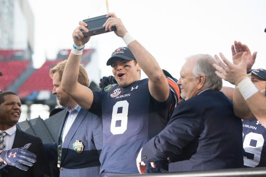 Auburn quarterback Jarrett Stidham (8) holds up his MVP trophy after the Music City Bowl at Nissan Stadium in Nashville, Tenn., on Friday, Dec. 28, 2018. Auburn defeated Purdue 63-14.