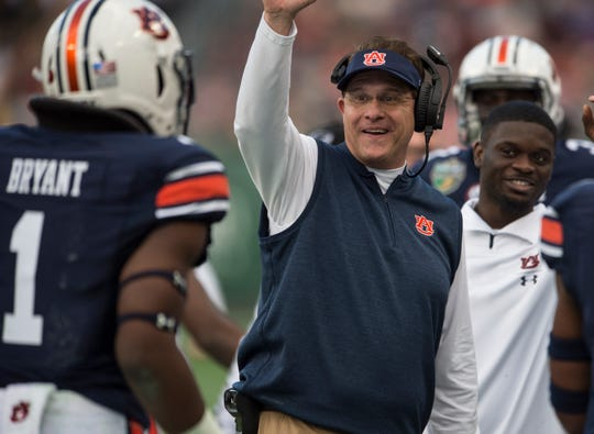 Auburn head coach Gus Malzahn celebrates with Auburn defensive lineman Big Kat Bryant (1) after Bryant's pick six during the Music City Bowl at Nissan Stadium in Nashville, Tenn., on Friday, Dec. 28, 2018. Auburn leads Purdue 56-7 at halftime.