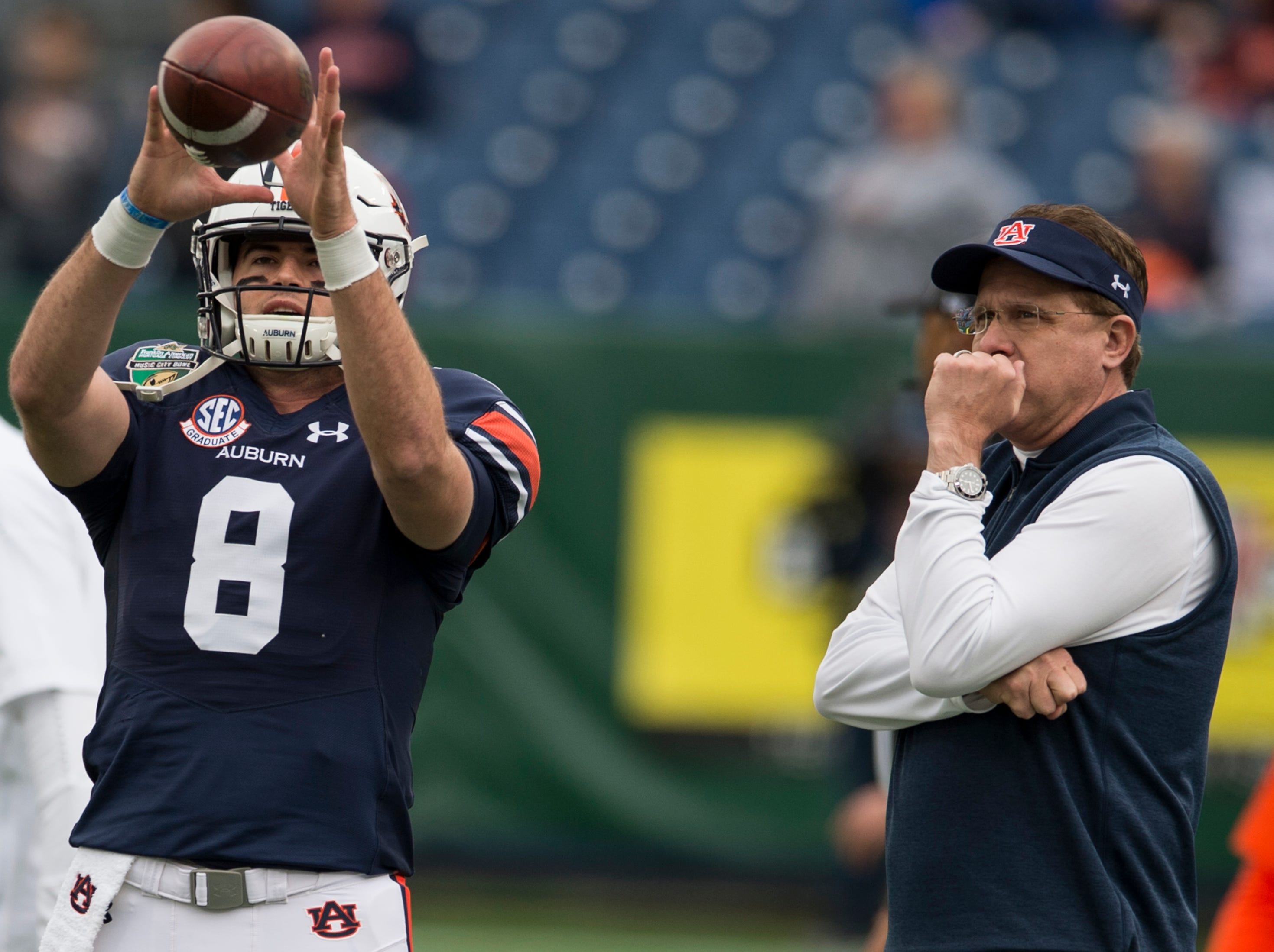 Auburn head coach Gus Malzahn watches on has quarterback Jarrett Stidham (8) warms up before the Music City Bowl at Nissan Stadium in Nashville, Tenn., on Friday, Dec. 28, 2018.