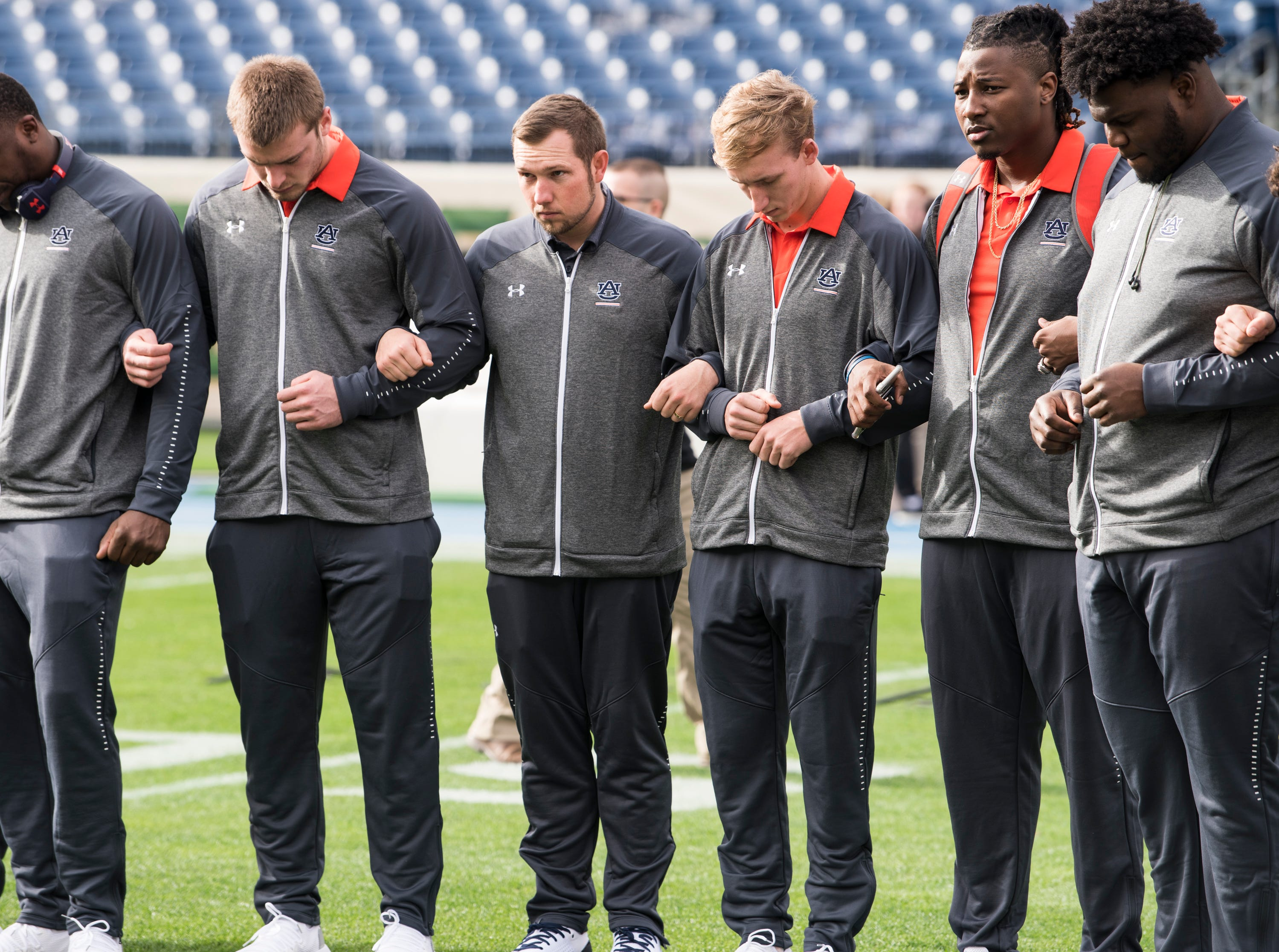 Auburn offensive coordinator Kenny Dillingham, middle, prays with the team before they take on Purdue in the Music City Bowl at Nissan Stadium in Nashville, Tenn., on Friday, Dec. 28, 2018.