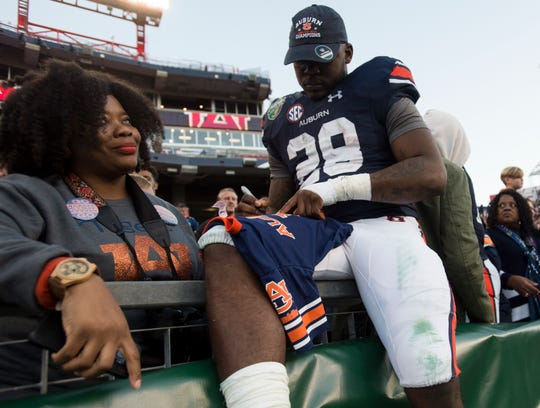 Auburn running back JaTarvious Whitlow (28) and his mom, Pamela Whitlow Holloway, celebrate after the Music City Bowl at Nissan Stadium in Nashville, Tenn., on Friday, Dec. 28, 2018. Auburn defeated Purdue 63-14.