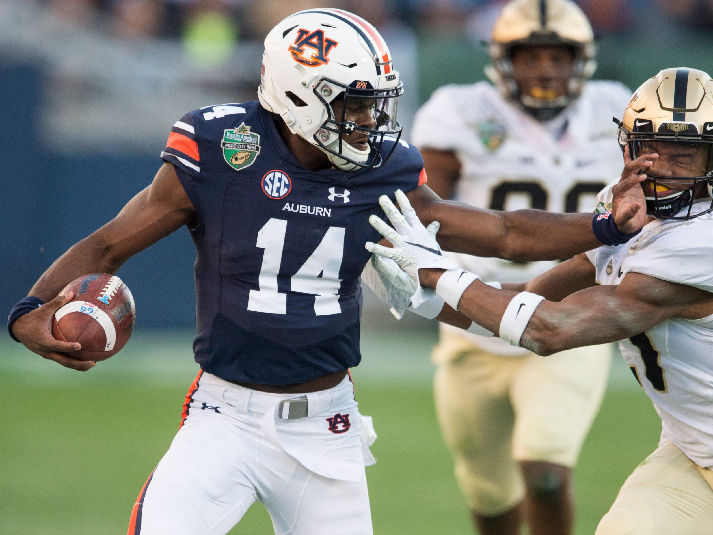 Auburn quarterback Malik Willis (14) stiff arms Purdue linebacker Markus Bailey (21) during the Music City Bowl at Nissan Stadium in Nashville, Tenn., on Friday, Dec. 28, 2018. Auburn defeated Purdue 63-14.