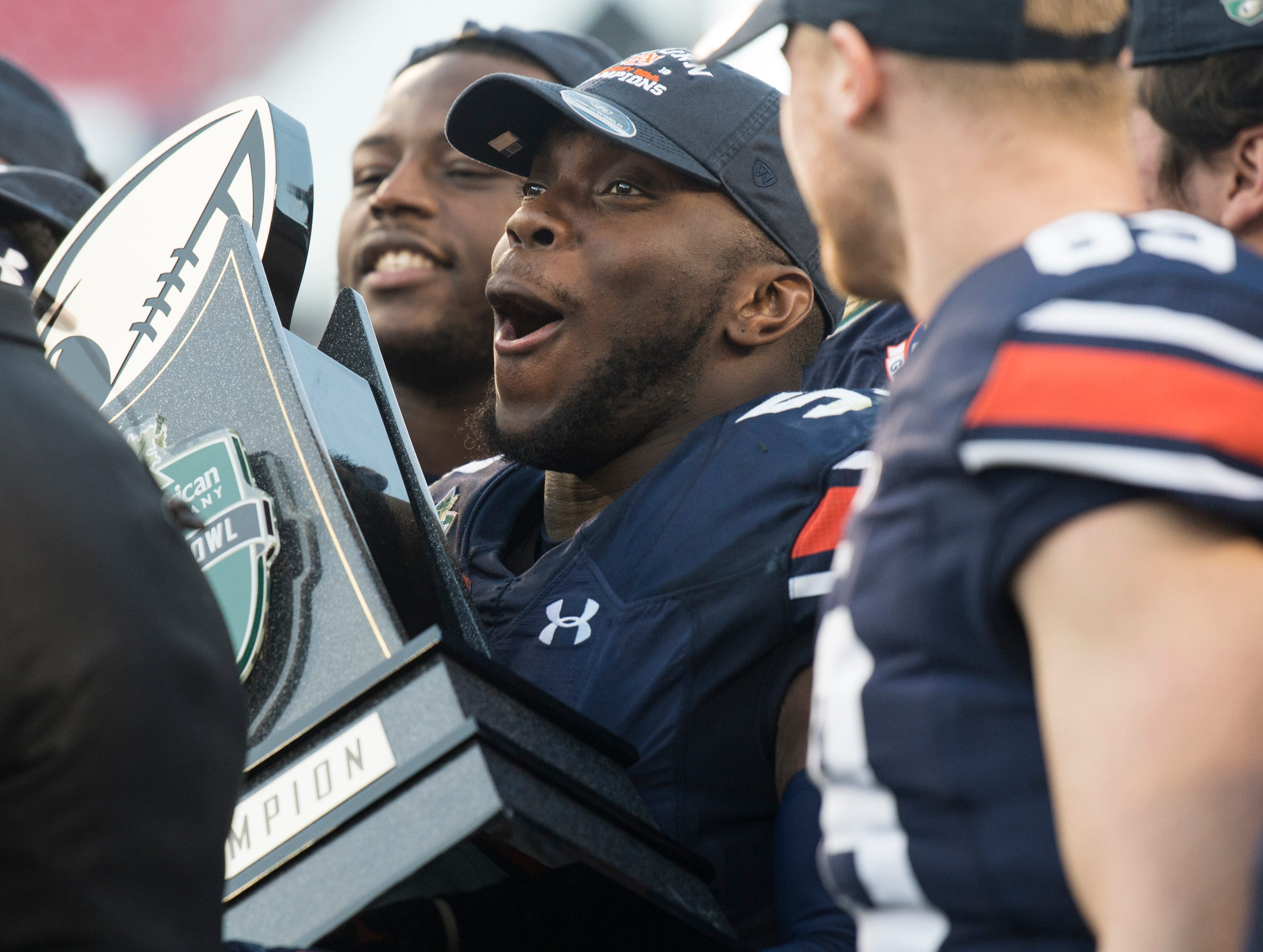 Auburn linebacker Deshaun Davis (57) holds the trophy after winning the Music City Bowl at Nissan Stadium in Nashville, Tenn., on Friday, Dec. 28, 2018. Auburn defeated Purdue 63-14.