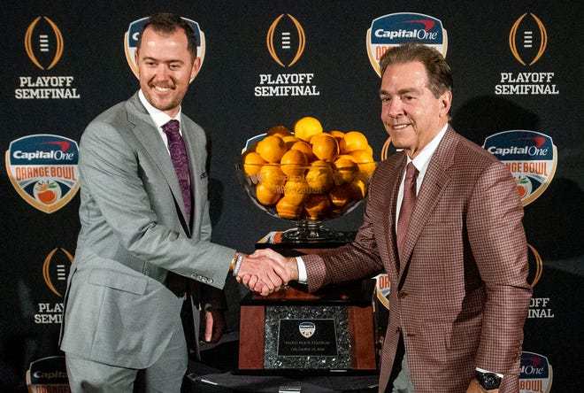 Oklahoma head coach Lincoln Riley and Alabama head coach Nick Saban greet each other in front of the trophy during the Orange Bowl Coaches Press Conference in Fort Lauderdale, Fla., on Friday December 28, 2018. Alabama plays Oklahoma in the Orange Bowl on Saturday.