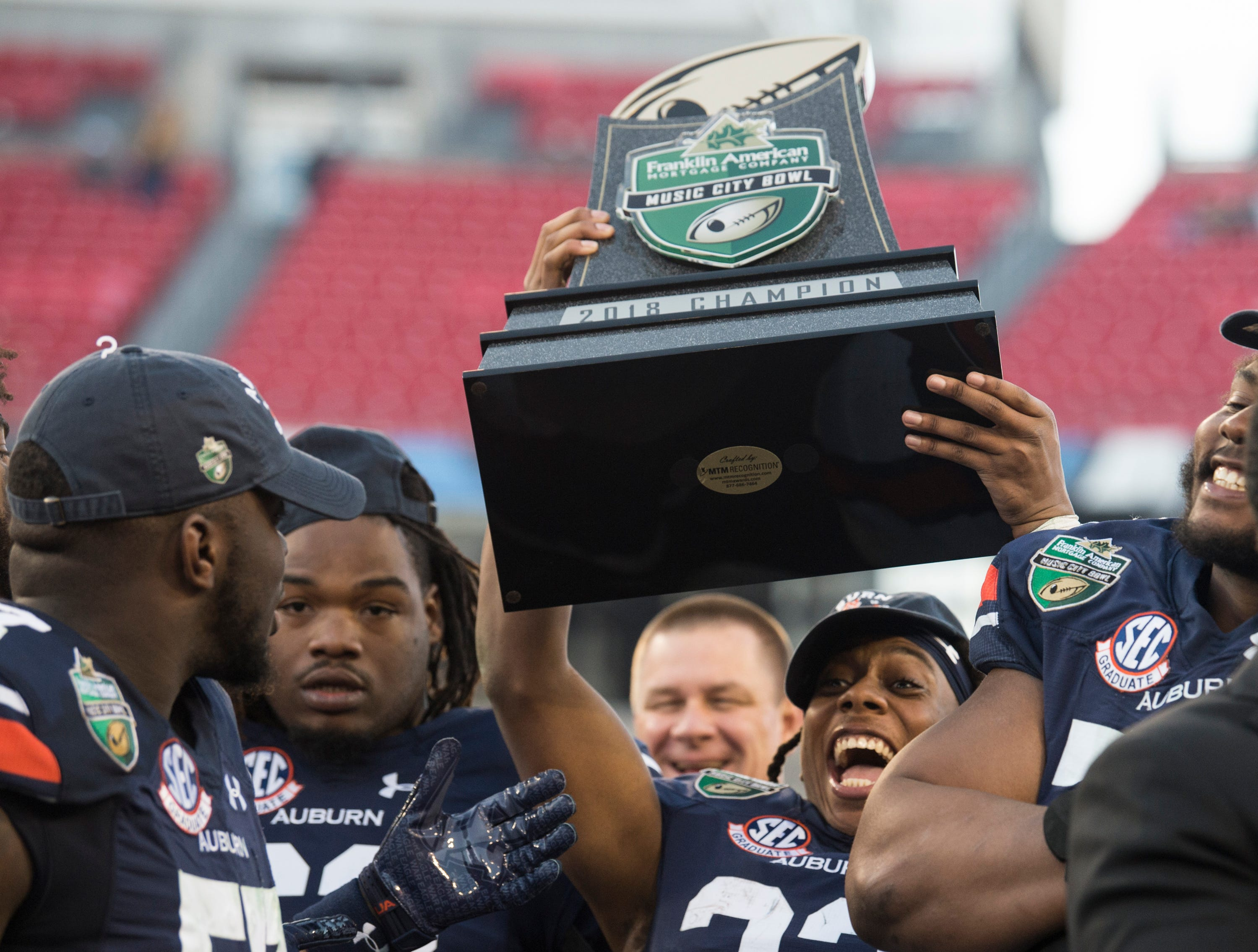 Auburn wide receiver Ryan Davis (23) holds up the trophy after winning the Music City Bowl at Nissan Stadium in Nashville, Tenn., on Friday, Dec. 28, 2018. Auburn defeated Purdue 63-14.
