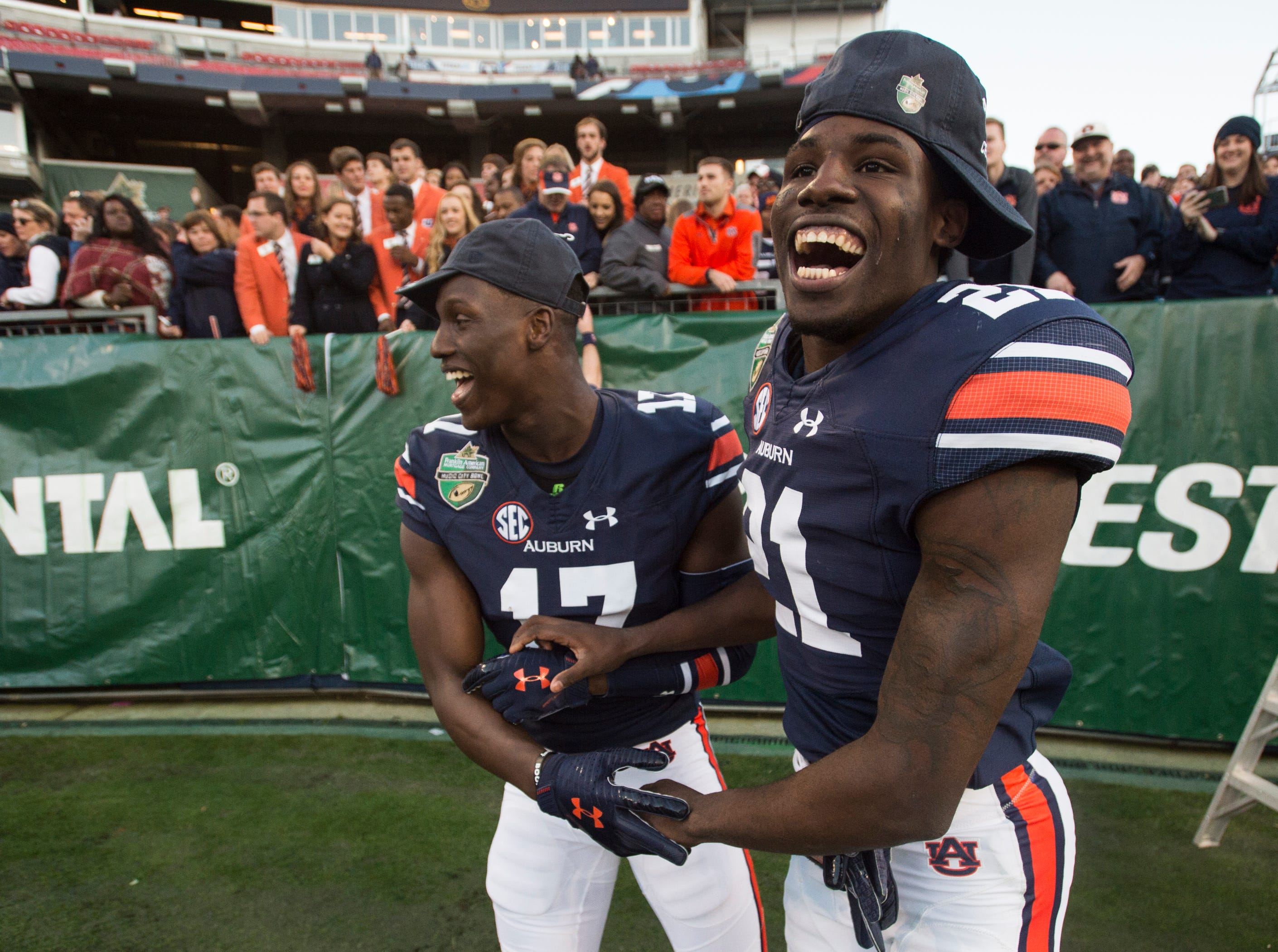 Auburn wide receiver Marquis McClain (17) and Auburn defensive back Smoke Monday (21) celebrate after the Music City Bowl at Nissan Stadium in Nashville, Tenn., on Friday, Dec. 28, 2018. Auburn defeated Purdue 63-14.