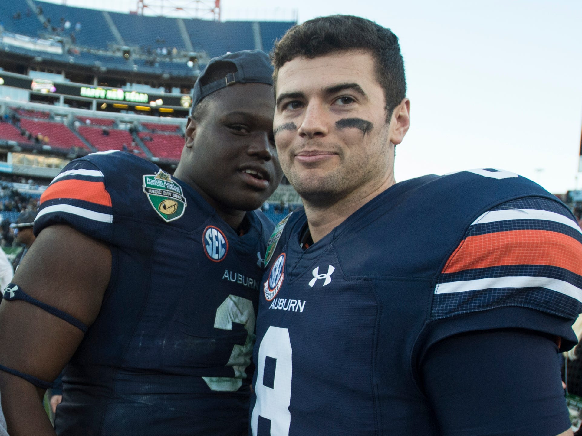 Auburn defensive lineman Marlon Davidson (3) and quarterback Jarrett Stidham (8) hug at the end of the game during the Music City Bowl at Nissan Stadium in Nashville, Tenn., on Friday, Dec. 28, 2018. Auburn defeated Purdue 63-14.