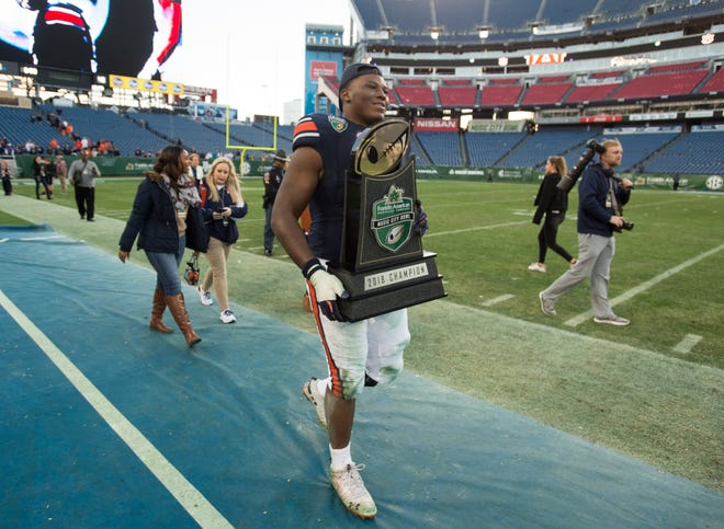 Auburn defensive lineman Derrick Brown (5) carries the trophy off the field after the Music City Bowl at Nissan Stadium in Nashville, Tenn., on Friday, Dec. 28, 2018. Auburn defeated Purdue 63-14.