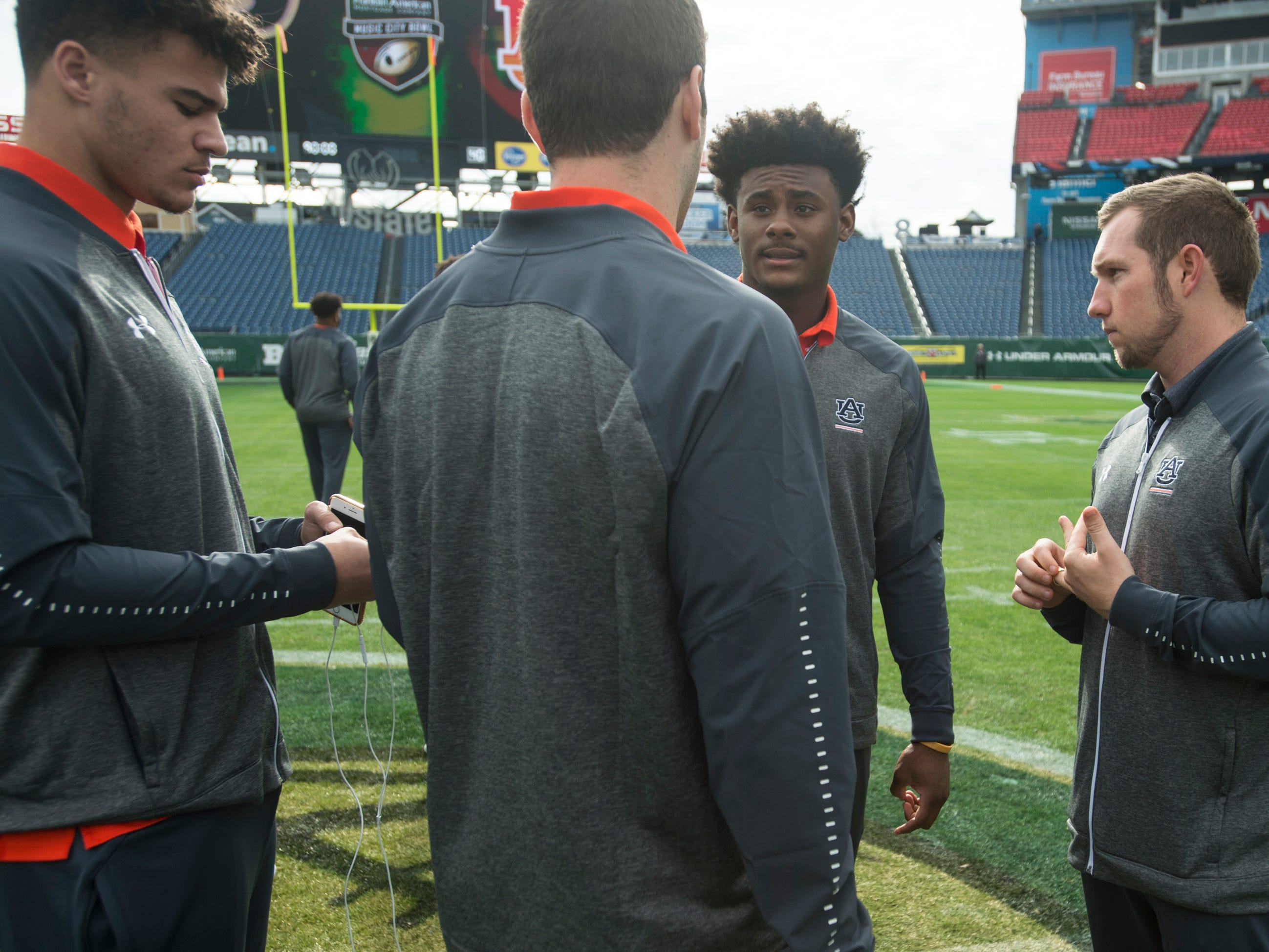 Auburn offensive coordinator Kenny Dillingham (far right) talks with quarterbacks Joey Gatewood (left), Jarrett Stidham (center) and Malik Willis (right) on the field before taking on Purdue in the Music City Bowl at Nissan Stadium in Nashville, Tenn., on Friday, Dec. 28, 2018.