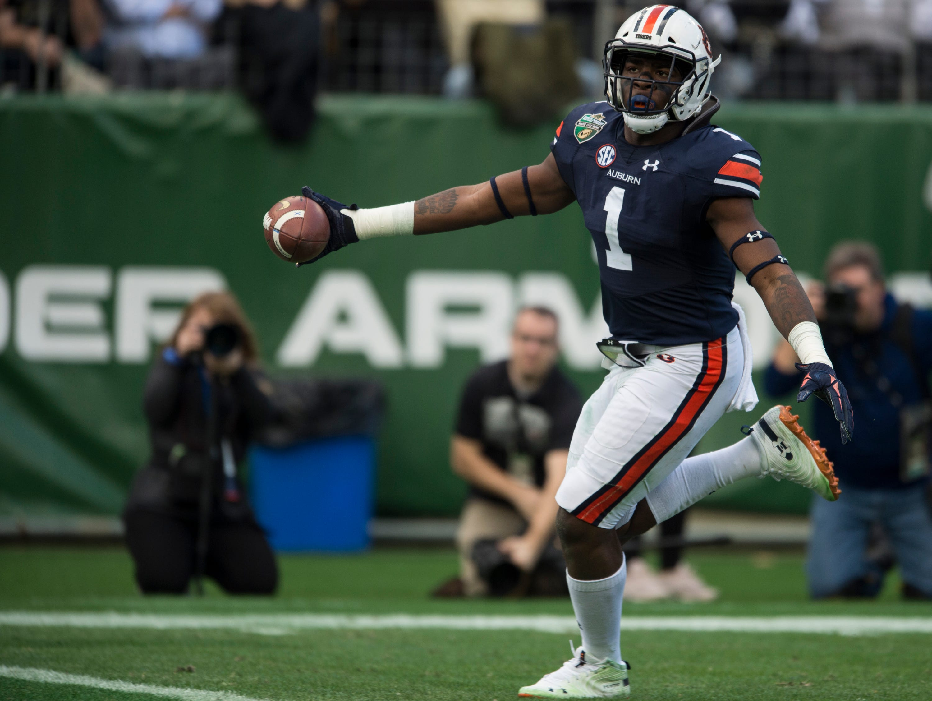 Auburn defensive lineman Big Kat Bryant (1) jogs into the end zone after intercepting a deflected pass during the Music City Bowl at Nissan Stadium in Nashville, Tenn., on Friday, Dec. 28, 2018. Auburn leads Purdue 56-7 at halftime.