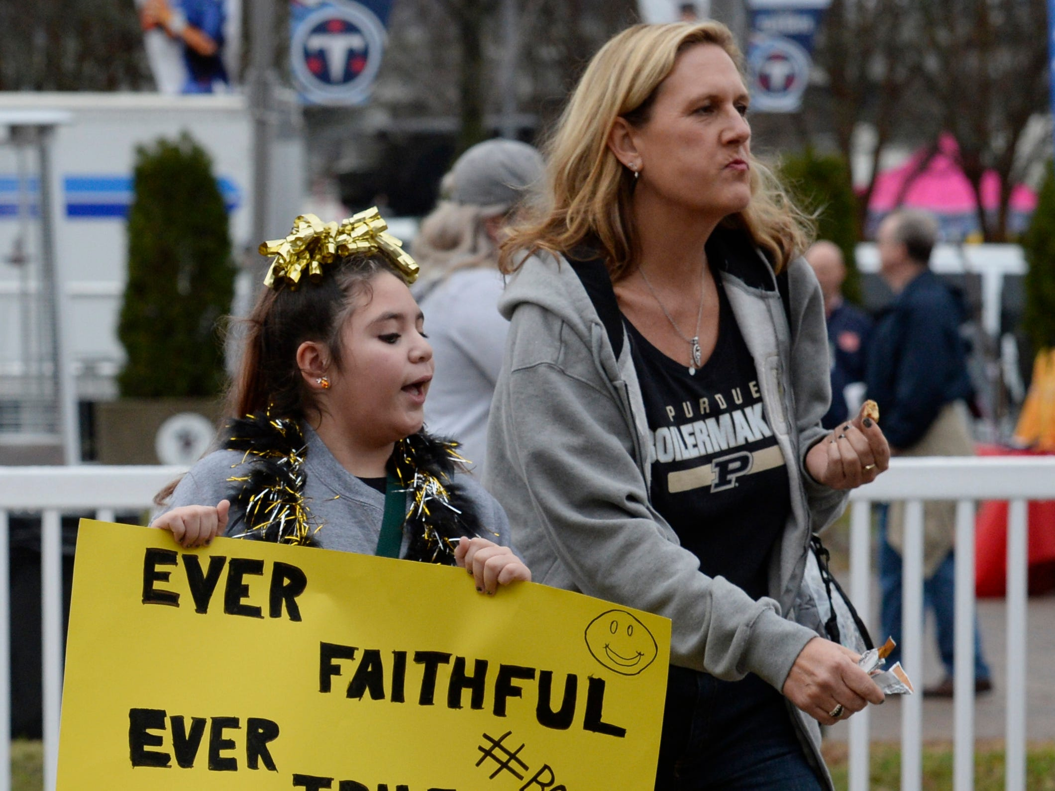 Elaina Hamilton carries a sign while walking with her aunt, Laurie Dreyling, before the start of the Music City Bowl NCAA college football game Friday, Dec. 28, 2018, at Nissan Stadium in Nashville, Tenn.