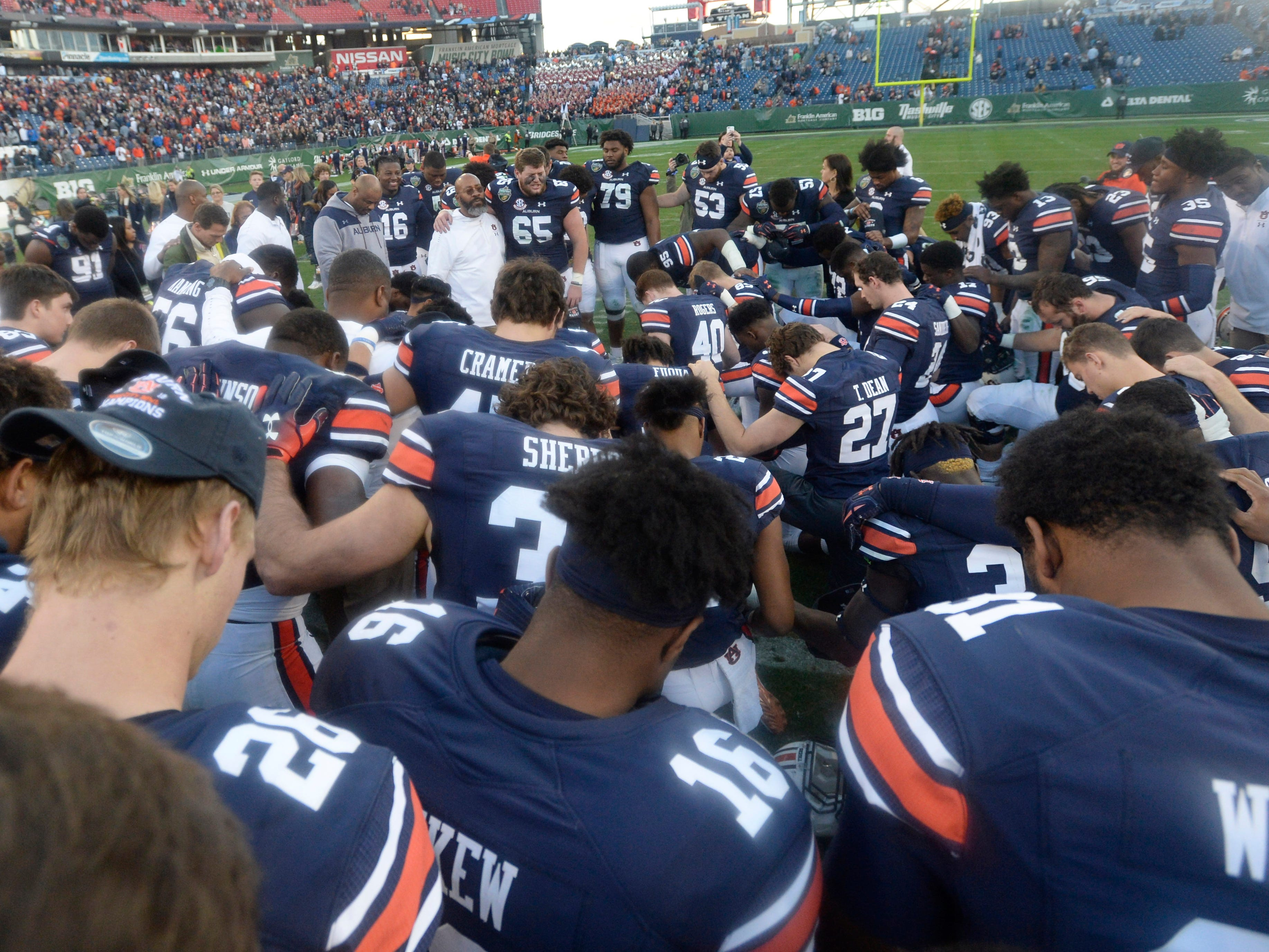 Auburn players and staff pray after the team's 63-14 win over Purdue in the Music City Bowl NCAA college football game Friday, Dec. 28, 2018, at Nissan Stadium in Nashville, Tenn.