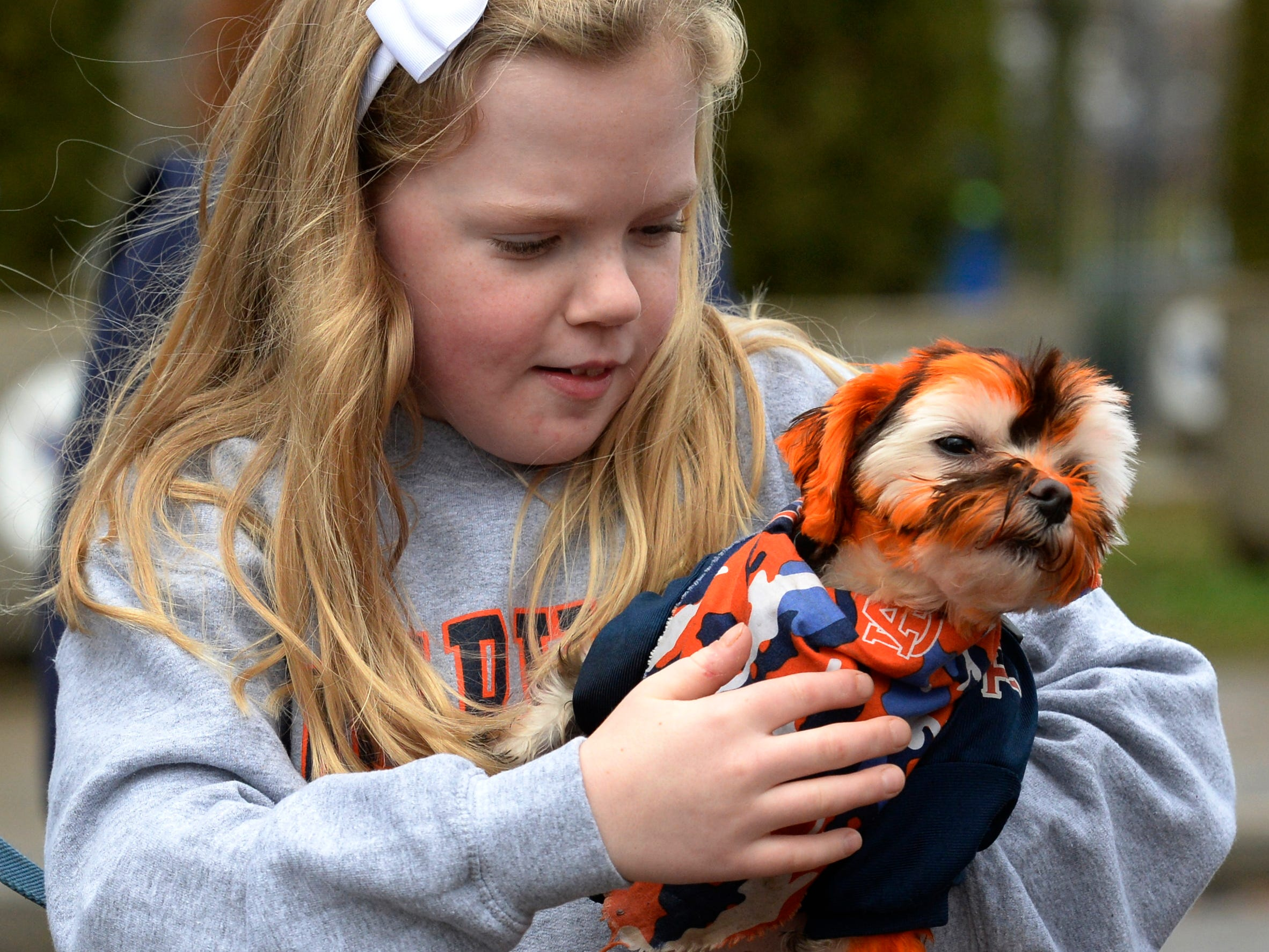 Madeline Lakoff holds Jake -- both of them decked out in Auburn colors -- before the start of the Music City Bowl NCAA college football game Friday, Dec. 28, 2018, at Nissan Stadium in Nashville, Tenn.