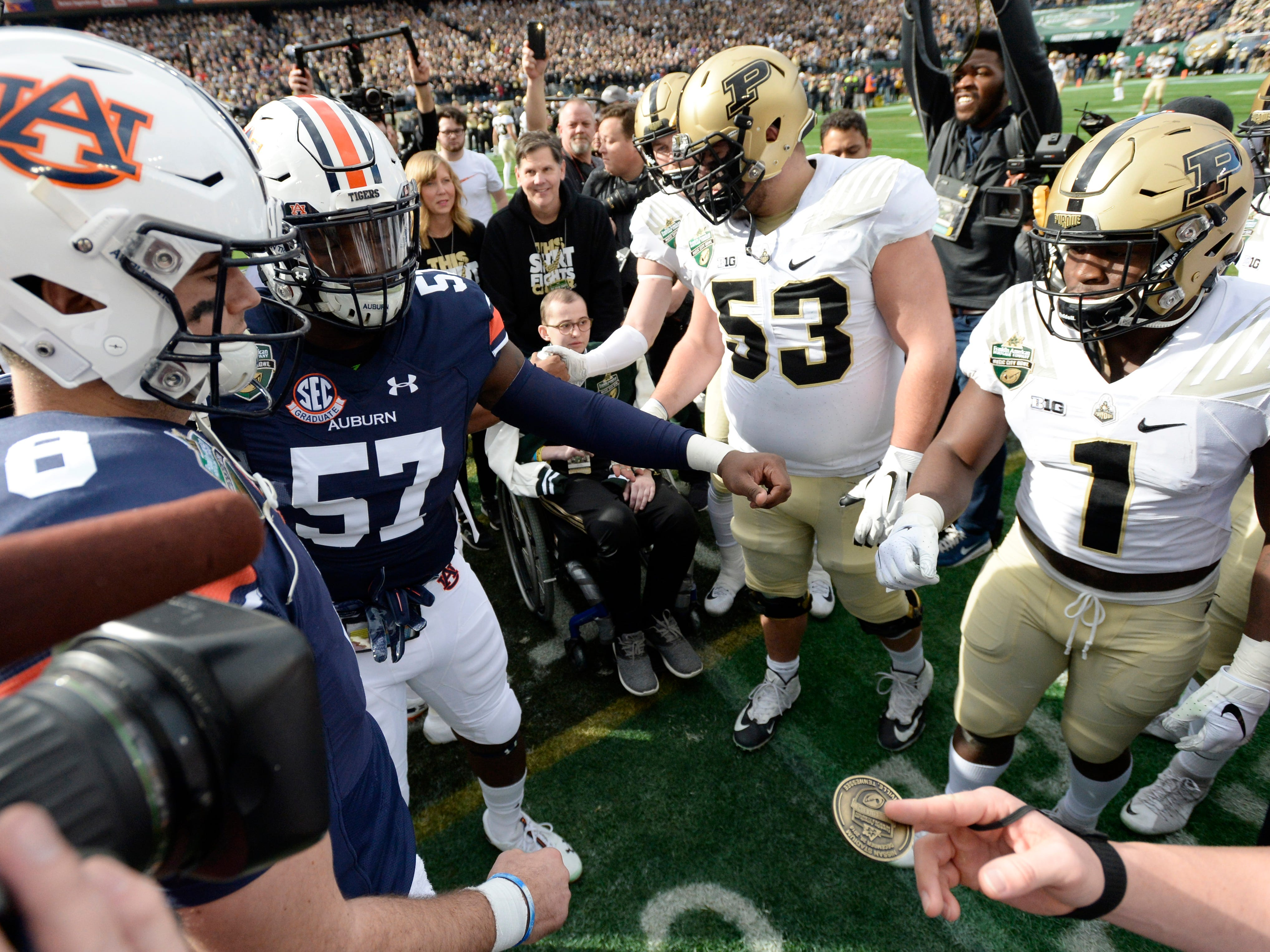 Auburn and Purdue players and Boilermakers honorary captain Tyler Trent gather for the coin toss before the start of the Music City Bowl NCAA college football game Friday, Dec. 28, 2018, at Nissan Stadium in Nashville, Tenn.