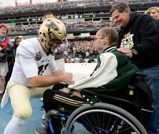 Purdue quarterback David Blough (11) greets honorary captain Tyler Trent before the start of the Music City Bowl NCAA college football game Friday, Dec. 28, 2018, at Nissan Stadium in Nashville, Tenn.