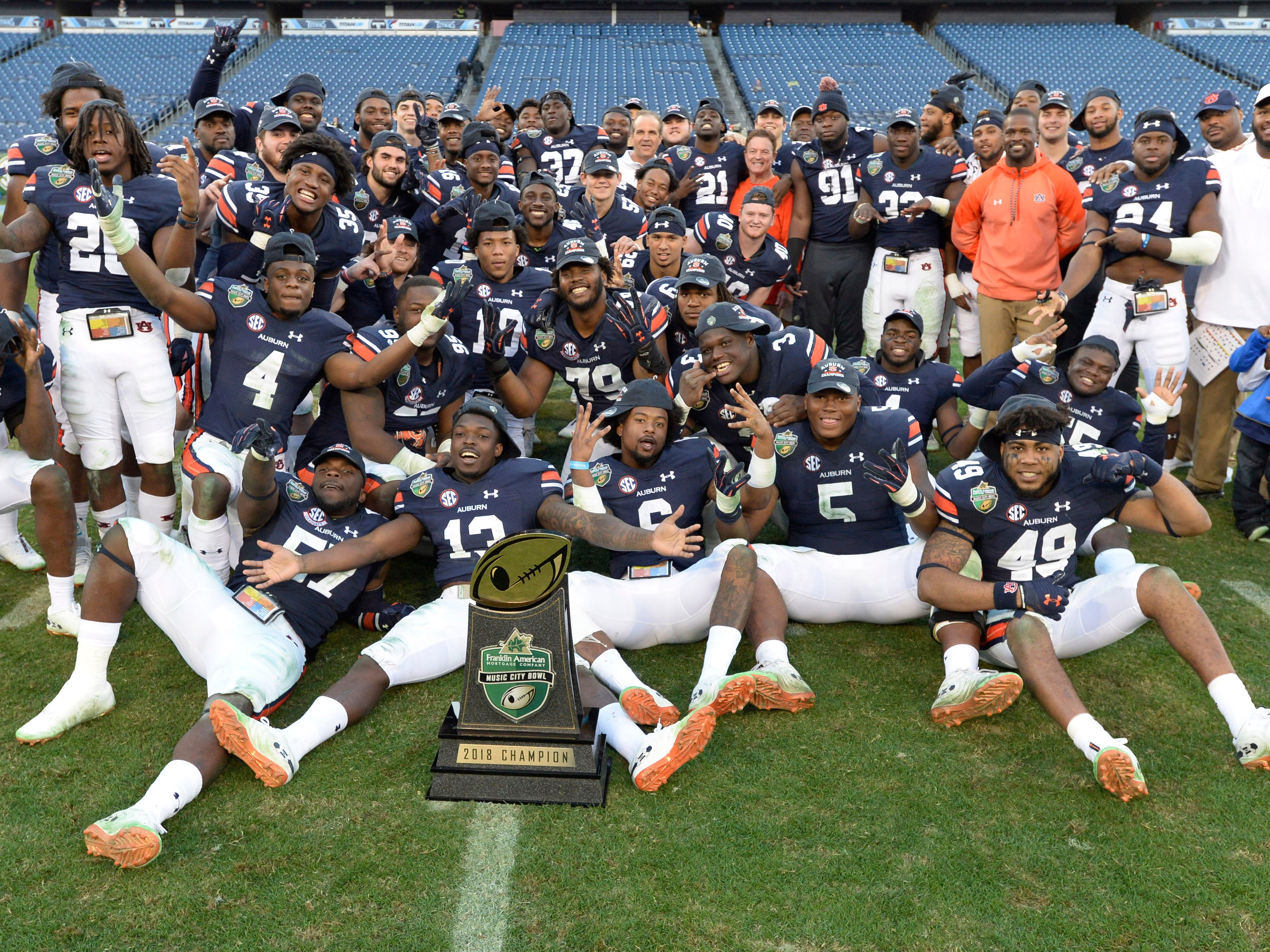 Auburn poses with the bowl trophy after beating Purdue 63-14 in the Music City Bowl NCAA college football game Friday, Dec. 28, 2018, at Nissan Stadium in Nashville, Tenn.