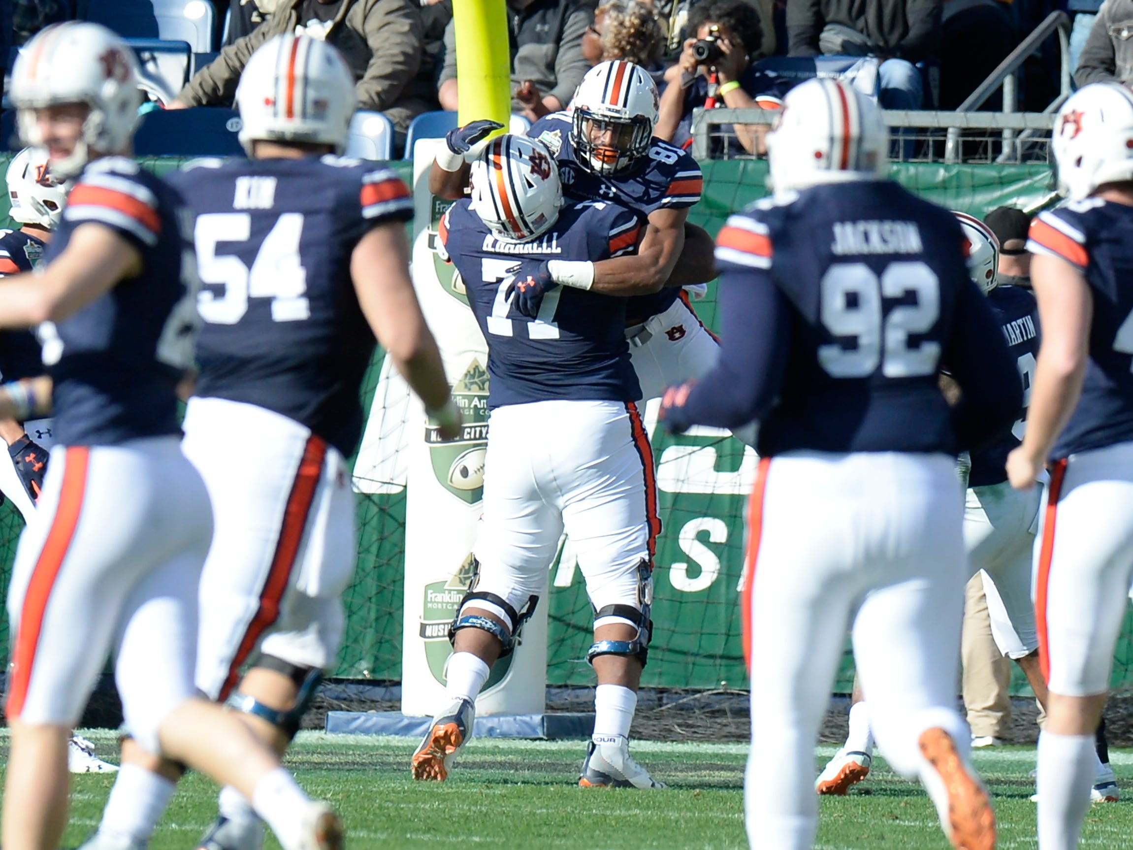 Auburn wide receiver Darius Slayton (81) celebrates his first touchdown with offensive lineman Marquel Harrell (77) in the first quarter of the Music City Bowl NCAA college football game Friday, Dec. 28, 2018, at Nissan Stadium in Nashville, Tenn.
