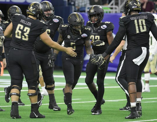 Vanderbilt Commodores running back Ke'Shawn Vaughn (5) is congratulated by his teammates after a 68-yard touchdown in the Texas Bowl on Thursday.