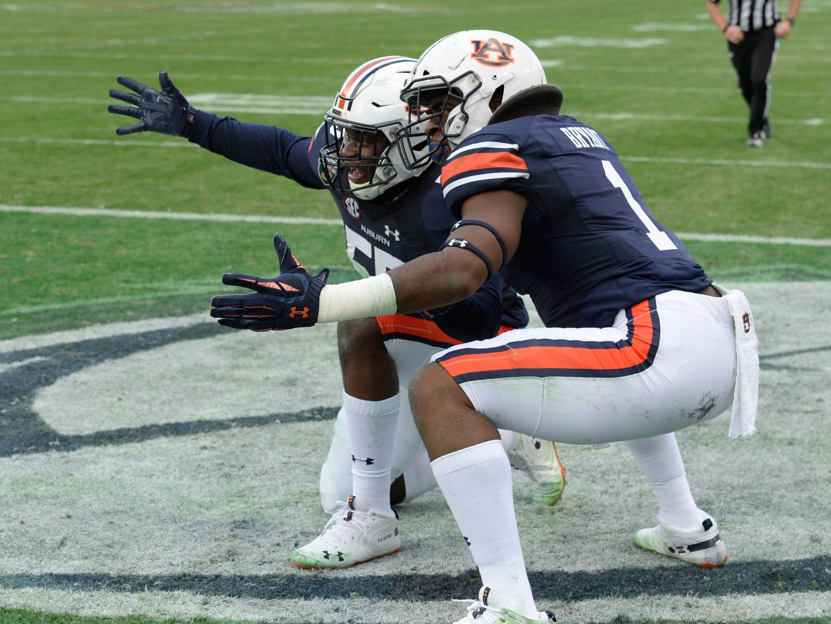 Auburn linebacker Big Kat Bryant (1) celebrates with linebacker T.D. Moultry (55) in the second quarter of the Music City Bowl NCAA college football game Friday, Dec. 28, 2018, at Nissan Stadium in Nashville, Tenn.