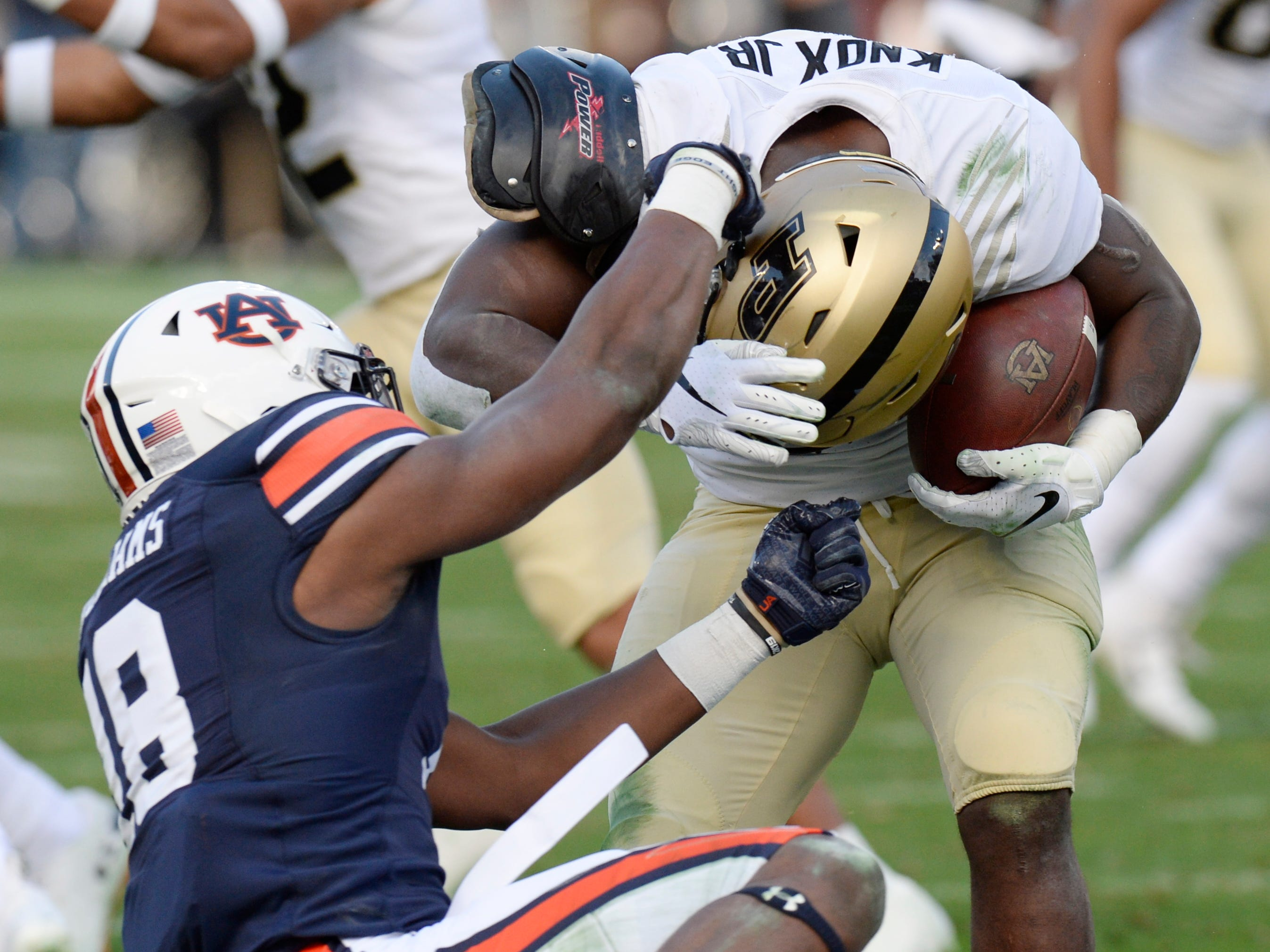 Auburn defensive back Jayvaughn Myers (18) brings down Purdue running back D.J. Knox (1) in the second quarter of the Music City Bowl NCAA college football game Friday, Dec. 28, 2018, at Nissan Stadium in Nashville, Tenn.