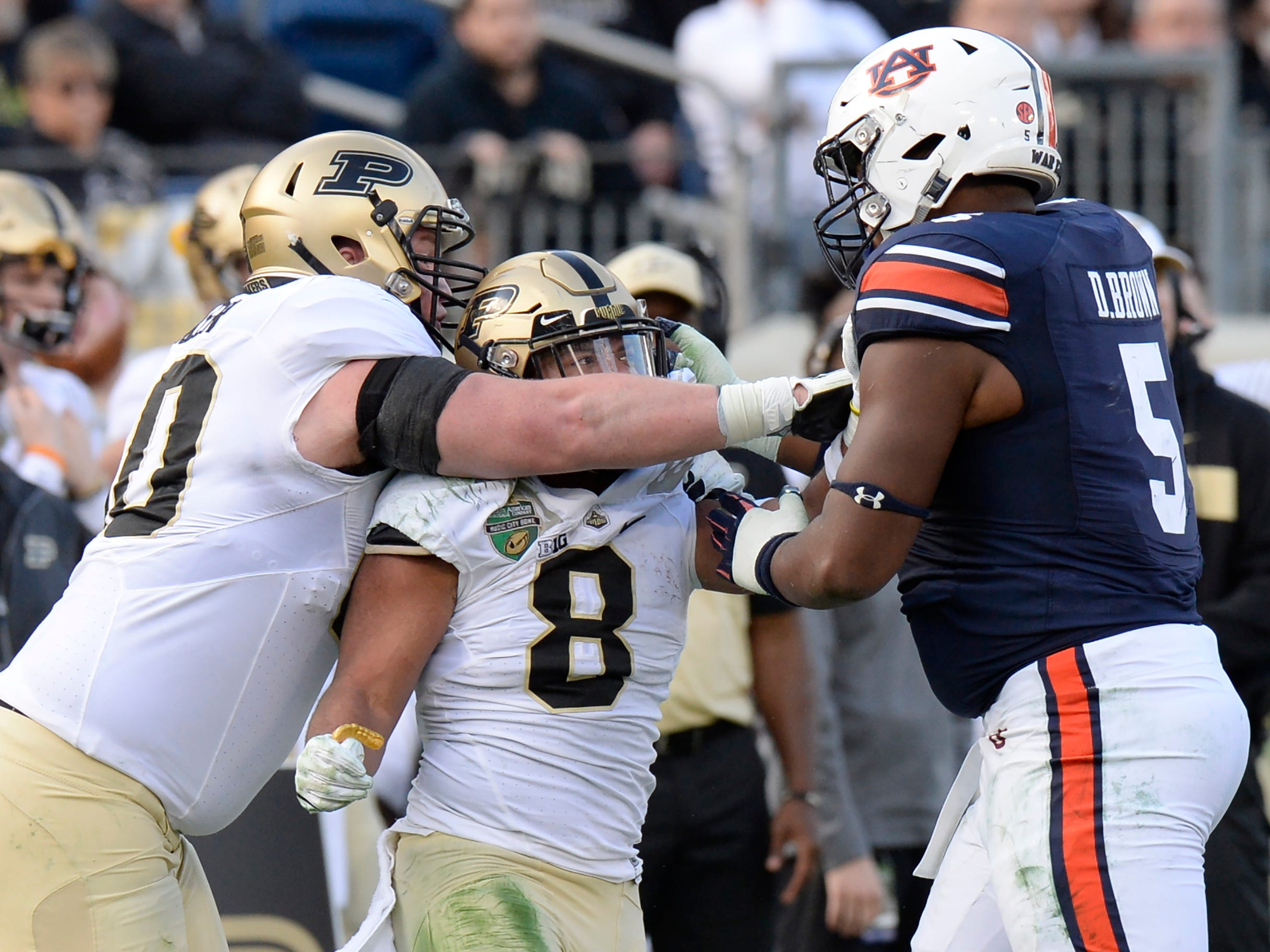 Purdue offensive lineman Will Bramel (70) and running back Markell Jones (8) mix it up with Auburn defensive lineman Derrick Brown (5) in the second quarter of the Music City Bowl NCAA college football game Friday, Dec. 28, 2018, at Nissan Stadium in Nashville, Tenn.