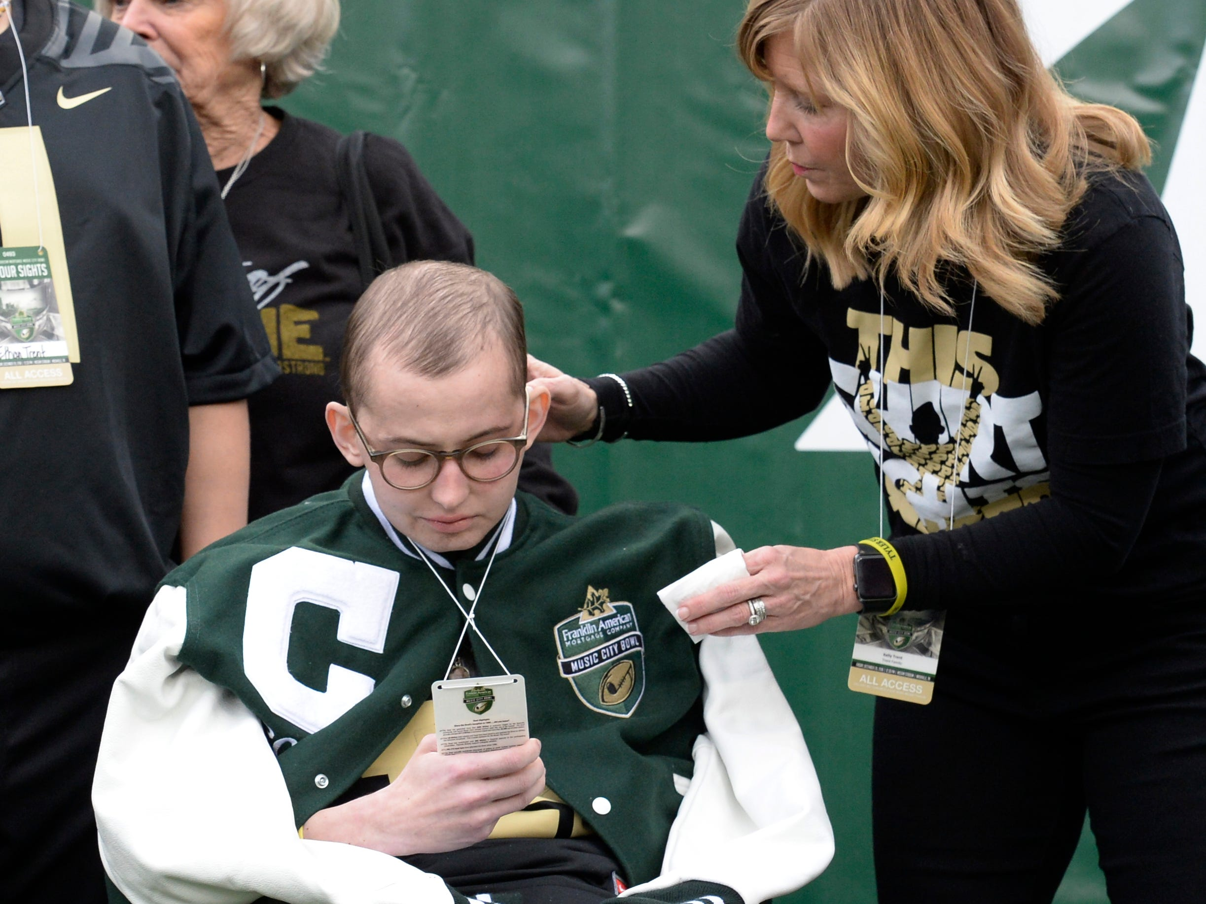 Purdue honorary captain Tyler Trent checks out his credential before the start of the Music City Bowl NCAA college football game Friday, Dec. 28, 2018, at Nissan Stadium in Nashville, Tenn.