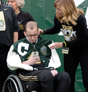 Purdue honorary captain Tyler Trent checks out his credential before the start of the Music City Bowl in Nashville on Friday.