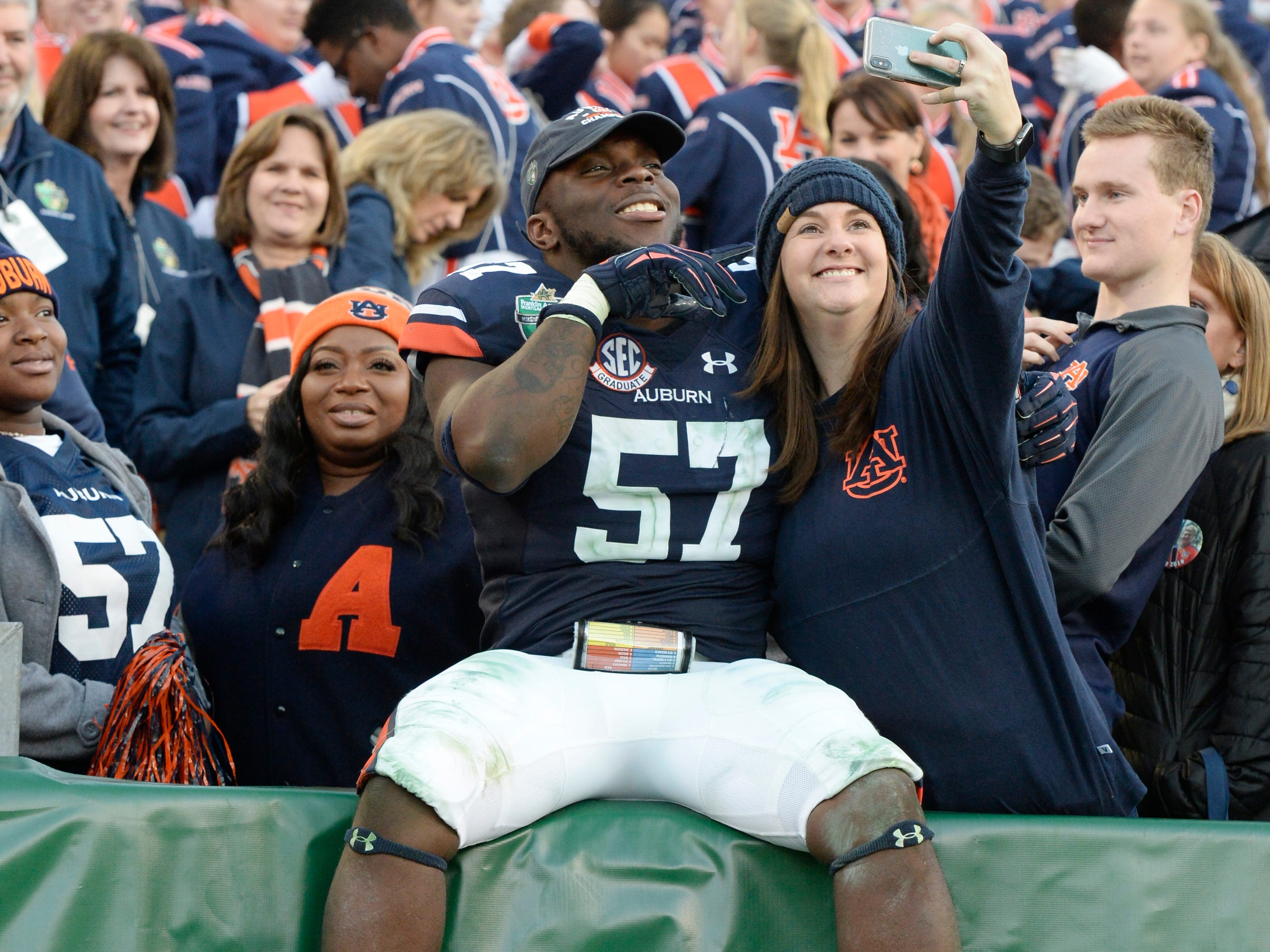 Auburn linebacker Deshaun Davis (57) celebrates in the stands after the team's win in the Music City Bowl NCAA college football game Friday, Dec. 28, 2018, at Nissan Stadium in Nashville, Tenn.