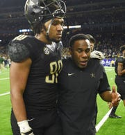 Vanderbilt head coach Derek Mason supports tight end Jared Pinkney after the team's 45-38 loss to Baylor in the Texas Bowl in Houston on Thursday.