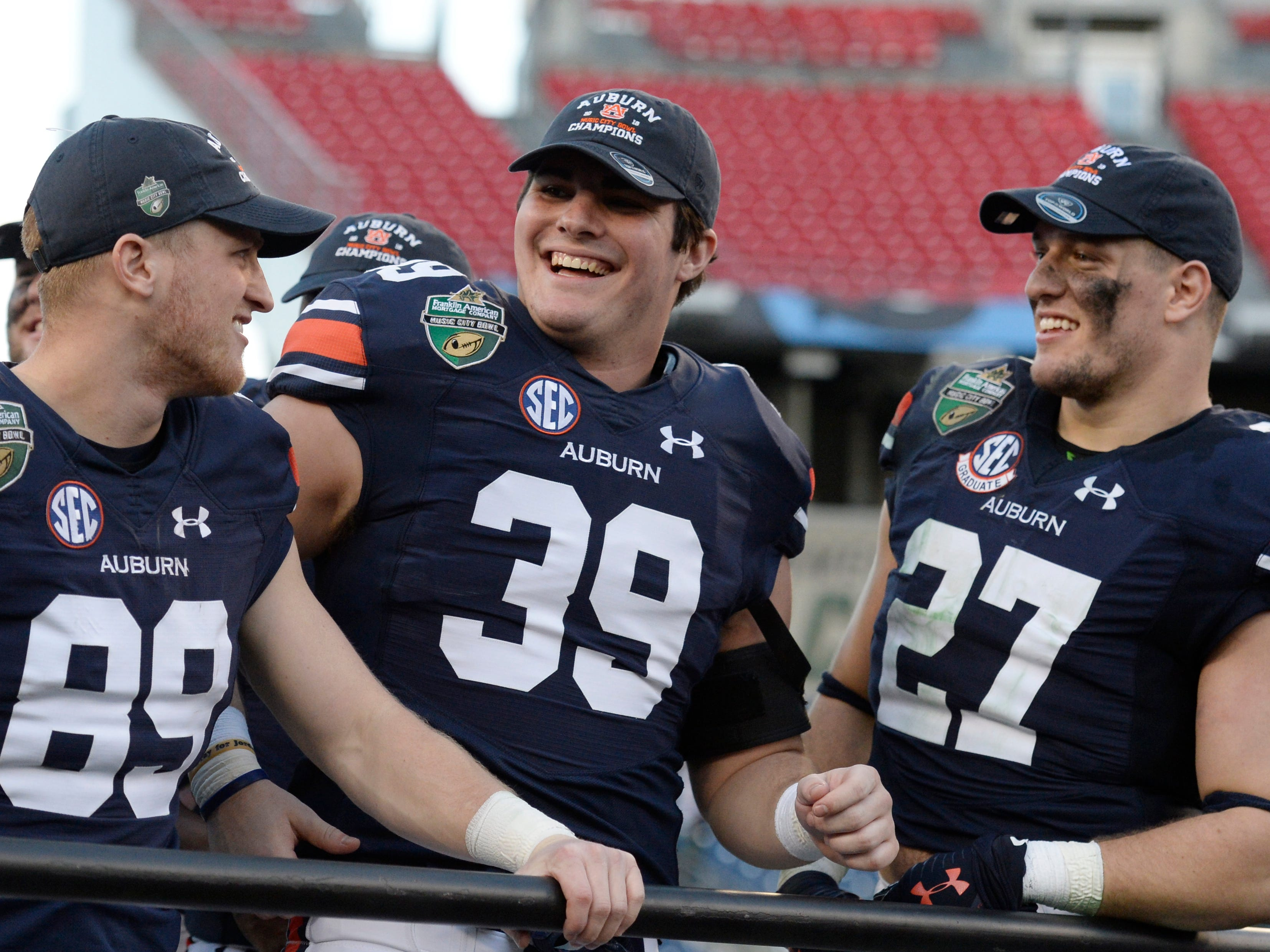 Auburn wide receiver Griffin King (89), tight end Robert Muschamp (39) and Chandler Cox (27) celebrate while waiting for the trophy presentation after the team's 63-14 win over Purdue in the Music City Bowl NCAA college football game Friday, Dec. 28, 2018, at Nissan Stadium in Nashville, Tenn.