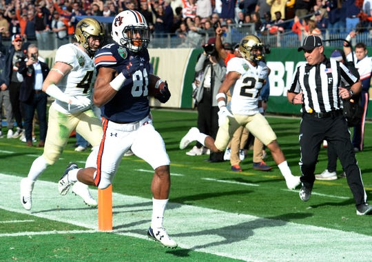 Auburn wide receiver Darius Slayton (81) scores one of his three touchdowns in the first half of the Music City Bowl NCAA college football game Friday, Dec. 28, 2018, at Nissan Stadium in Nashville, Tenn.
